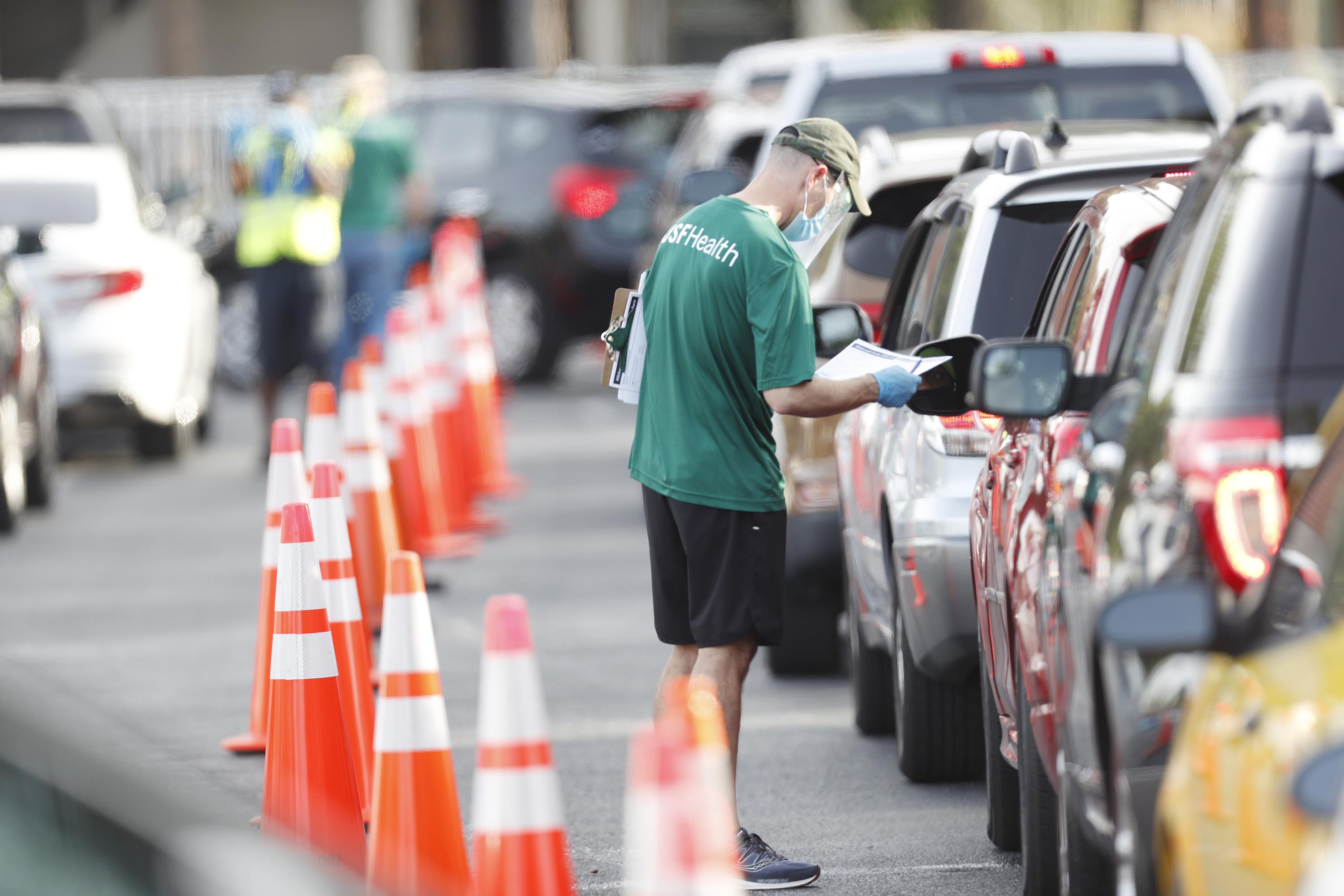 A University of South Florida (USF) Health administrator talks to a driver before they receive a coronavirus test in Tampa, Florida, on June 25.