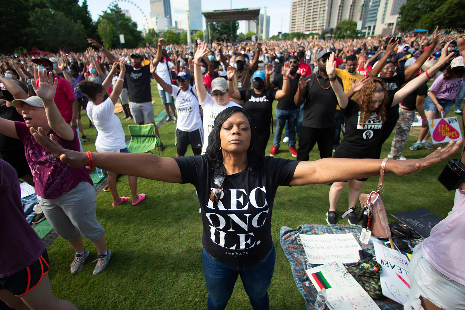 A woman prays during an event hosted by OneRace Movement at Atlanta's Centennial Olympic Park to commemorate Juneteenth on Friday, June 19, 2020.
