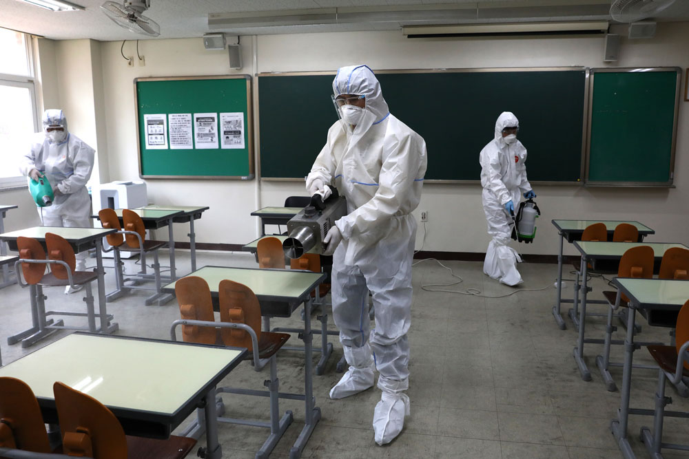 Disinfection professionals and government officials wearing protective clothing spray antiseptic solution in a classroom to prevent the spread of Covid-19 ahead of school reopening on May 11 in Seoul.