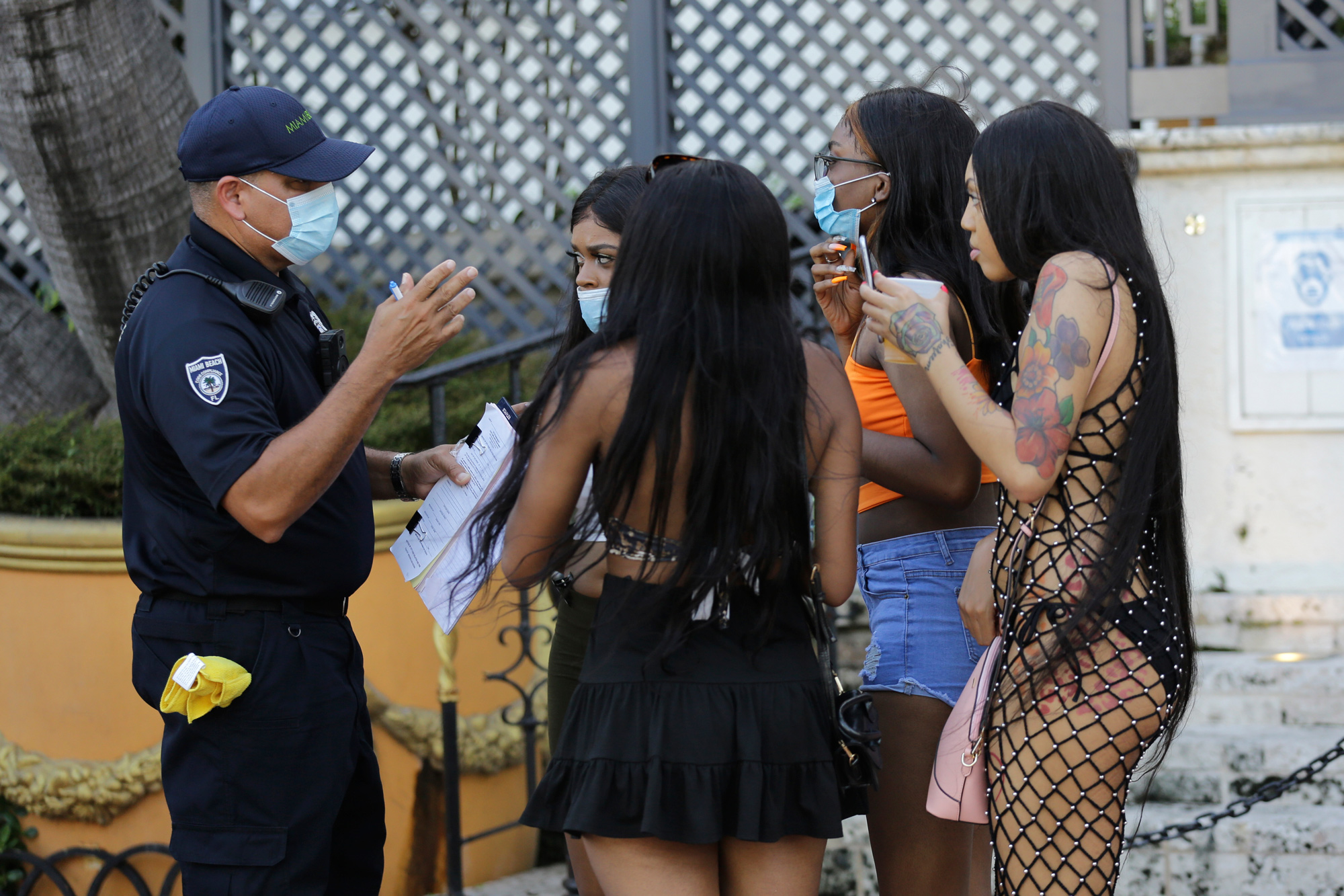 Luis Negron, a Miami Beach code compliance officer, left, talks with women along Ocean Drive about wearing a protective face mask on July 24 in Miami Beach, Florida.