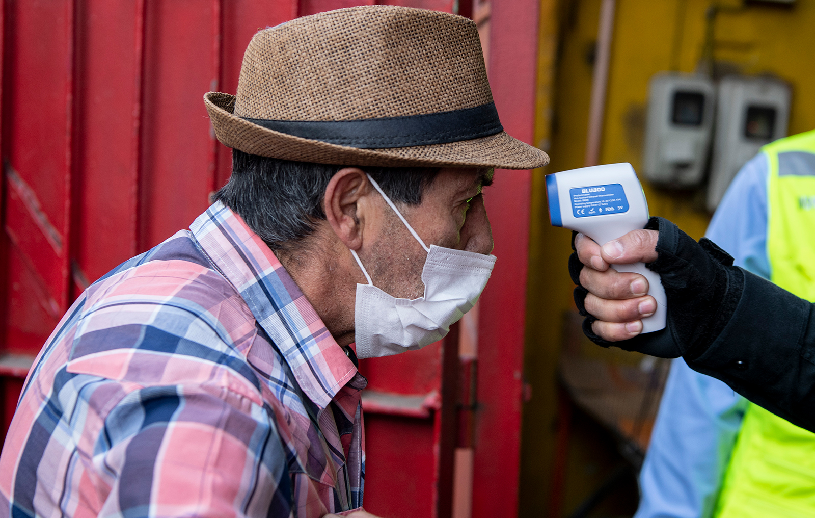 A security guard checks the bodytemperature of a man wearing a face mask in Santiago, on Wednesday, May 6.