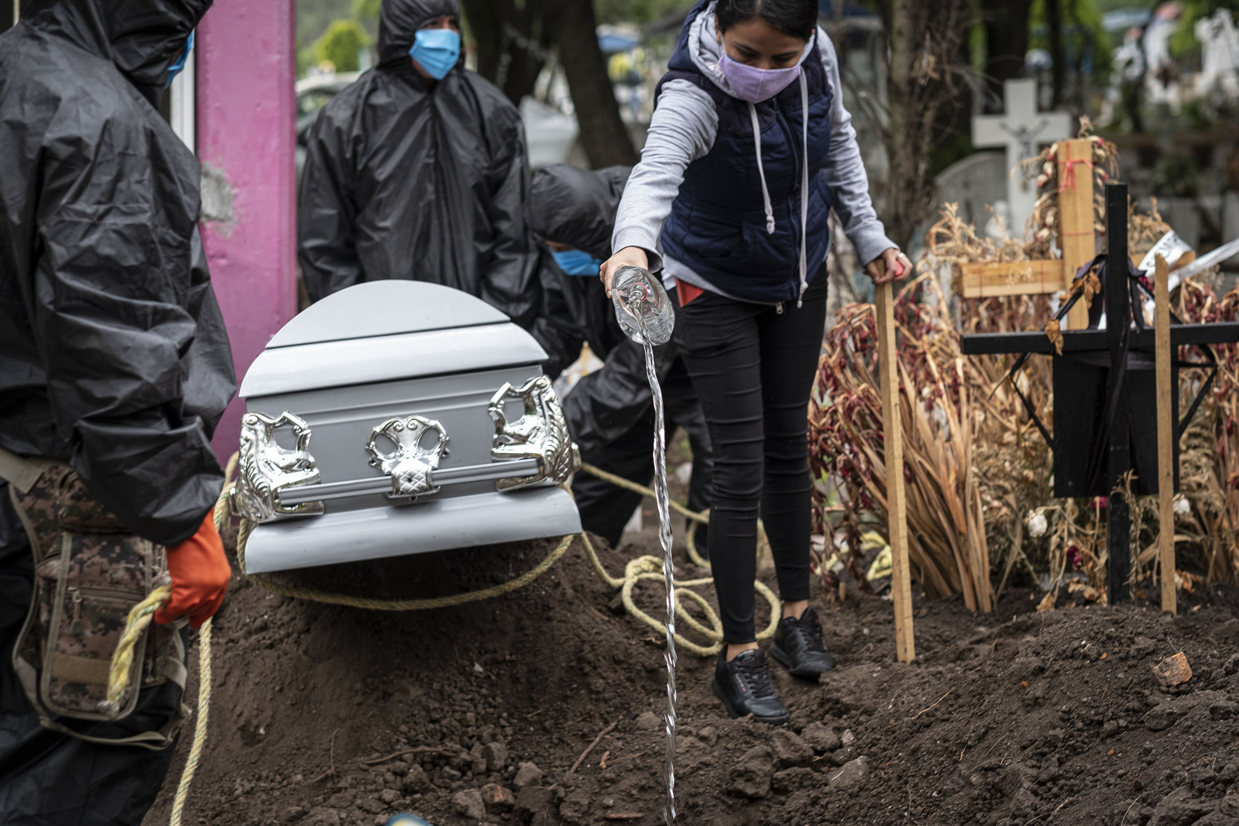 A woman wearing a face mask pours holy water into a grave during the funeral of a COVID 19 death victim at the San Isidro cemetery in Mexico, on June 24.