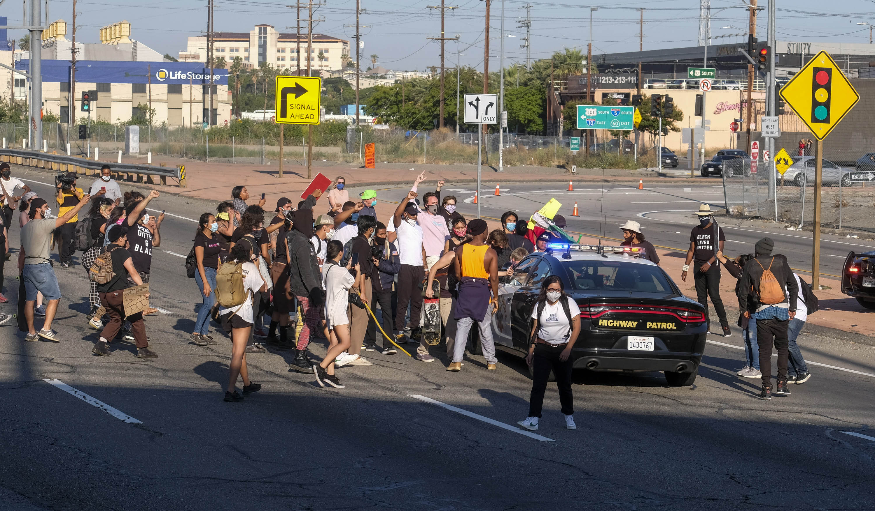 Demonstrators attack a California Highway Patrol cruiser in the Hollywood Freeway in Los Angeles on Wednesday, May 27.