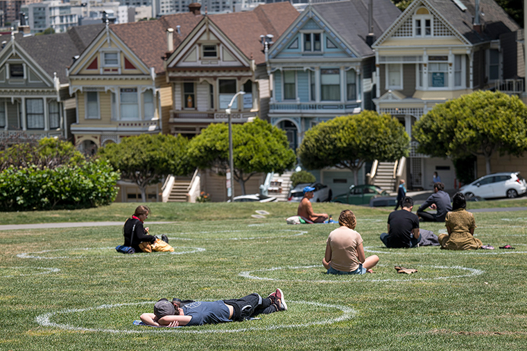 People sit on the grass in circles drawn to promote social distancing at Alamo Square in San Francisco on June 11.