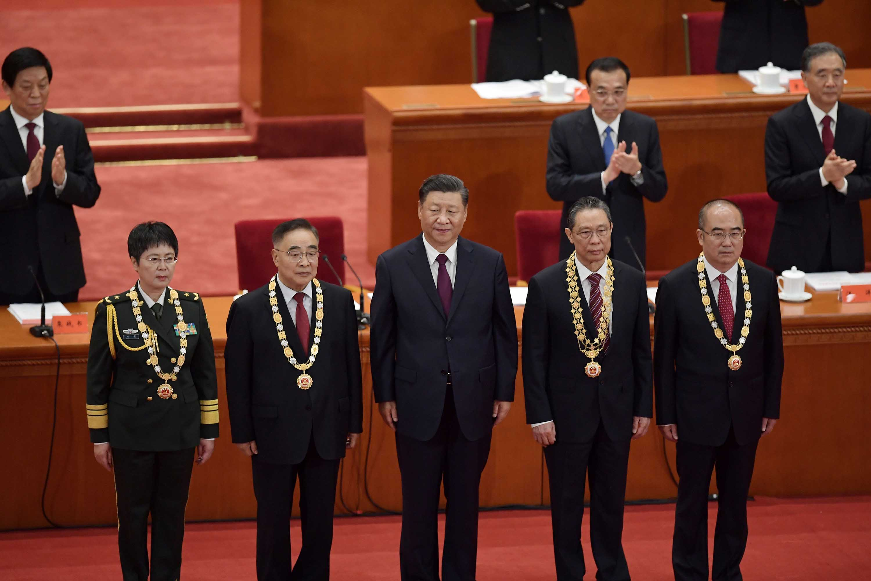Chinese President Xi Jinping, center, stands with honourees (from left) Chen Wei, Zhang Boli, Zhong Nanshan, and Zhang Dingyu, as they receive awards during a ceremony to honor people who fought against the pandemic, in Beijing, on September 8.