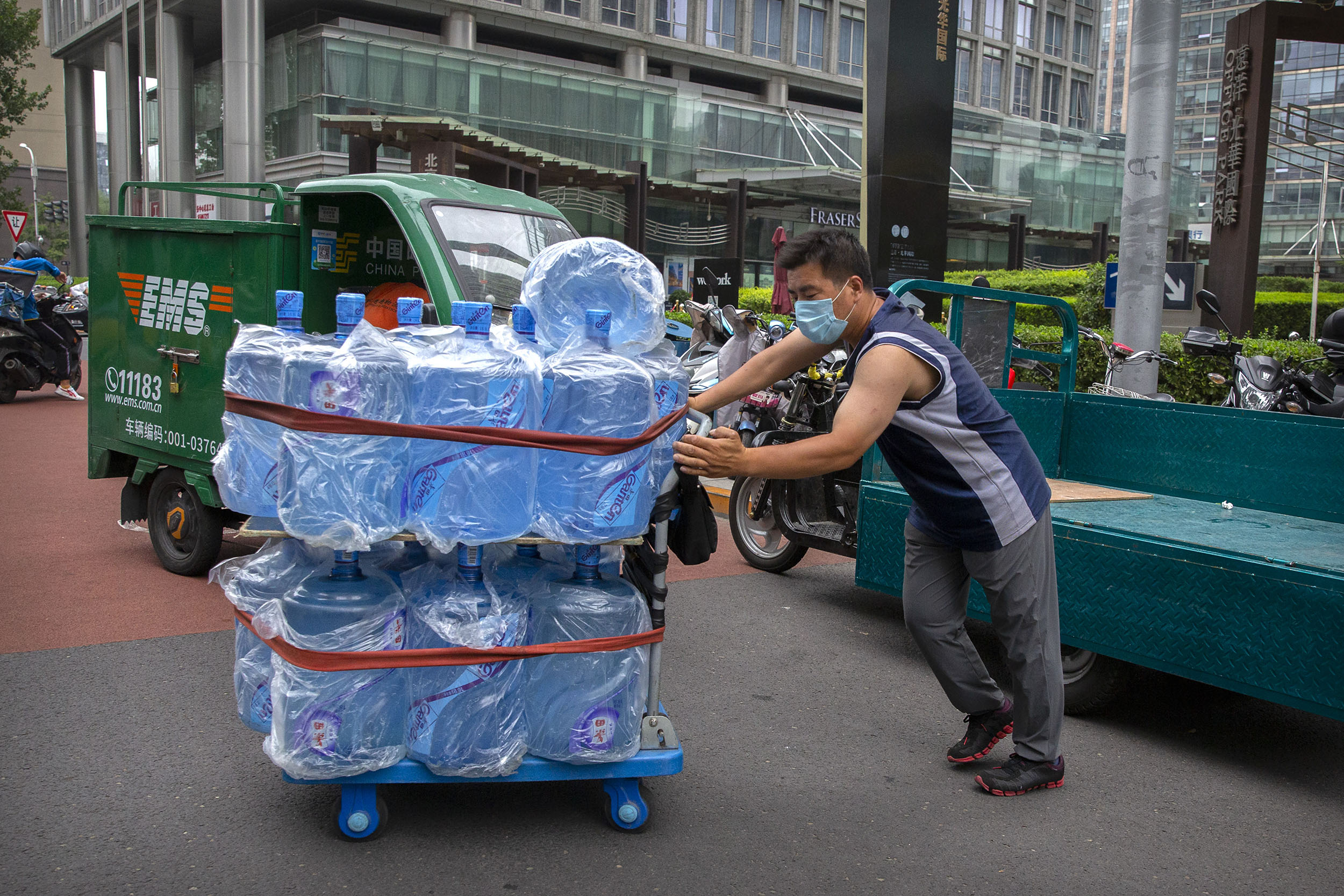 A worker pushes a cart loaded with bottles of drinking water in Beijing on July 17.