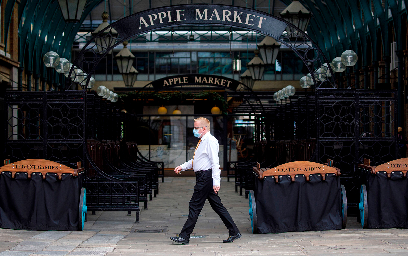 A man wearing a face mask walks in an empty Covent Garden in London on June 15.