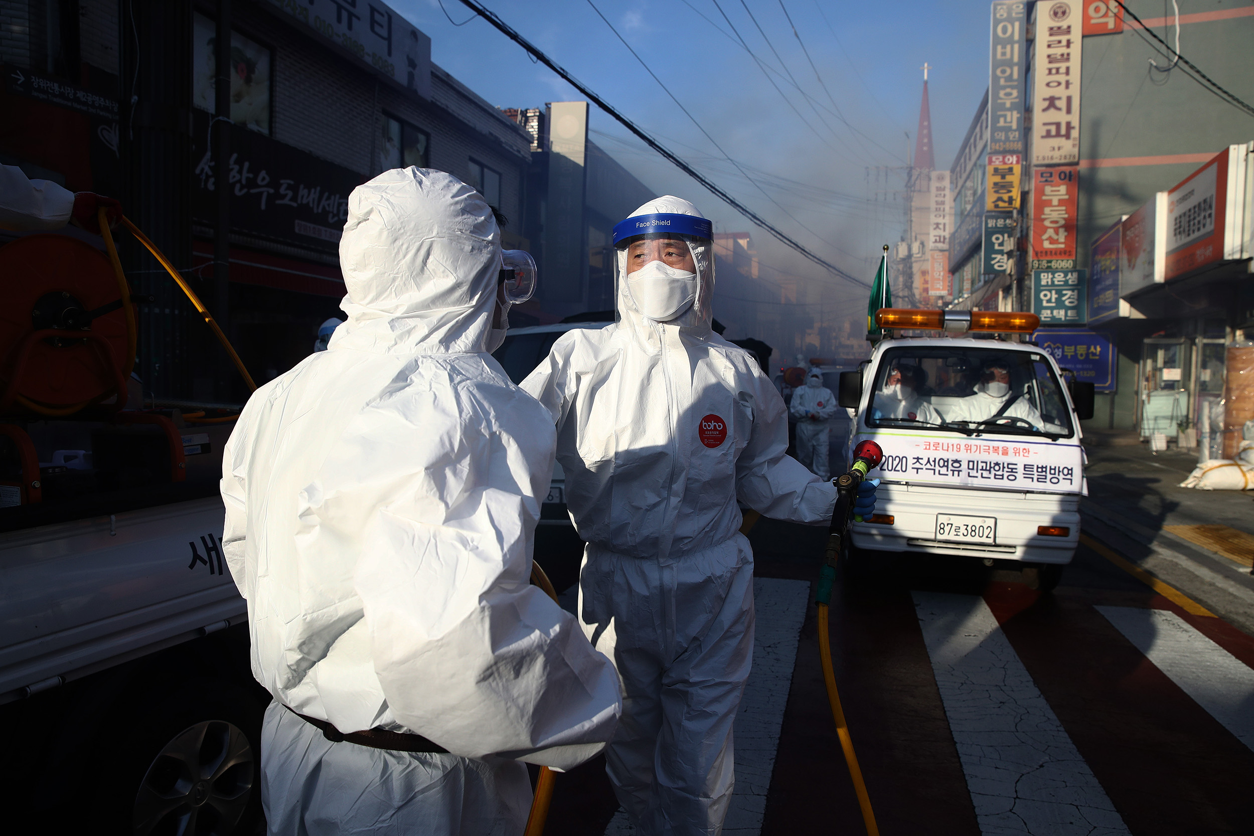 Workers wearing personal protective equipment disinfect a street to preventthe spread of coronavirus on October 6, in Seoul, South Korea.
