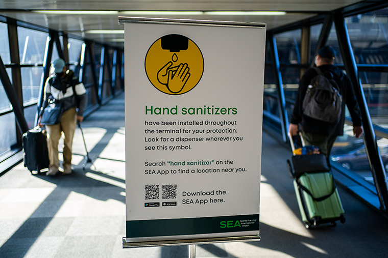 Travelers pass by a sign advertising hand sanitizer at Seattle-Tacoma International Airport on November 29, 2020 in SeaTac, Washington.