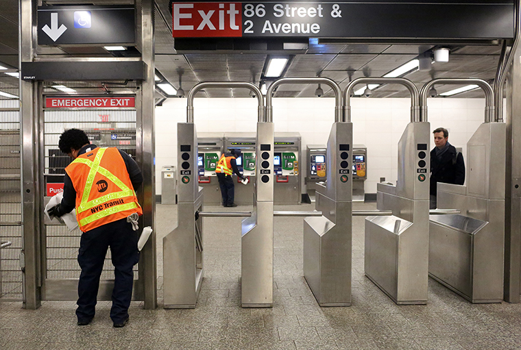 MTA cleaning staff disinfect the 86th St. Q train station on March 4, in New York City.