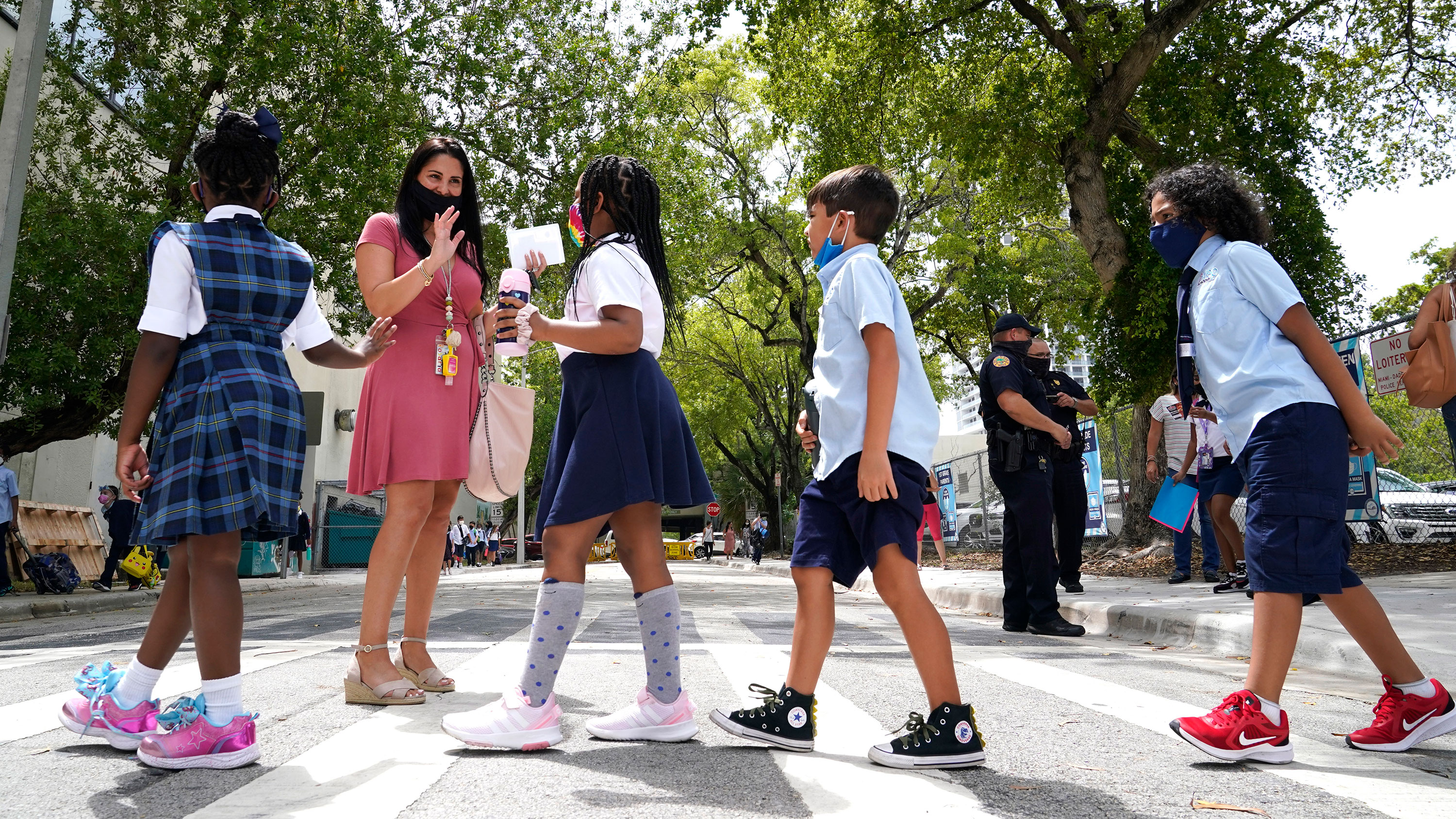 A teacher greets students outside of a school in Miami on August 23.