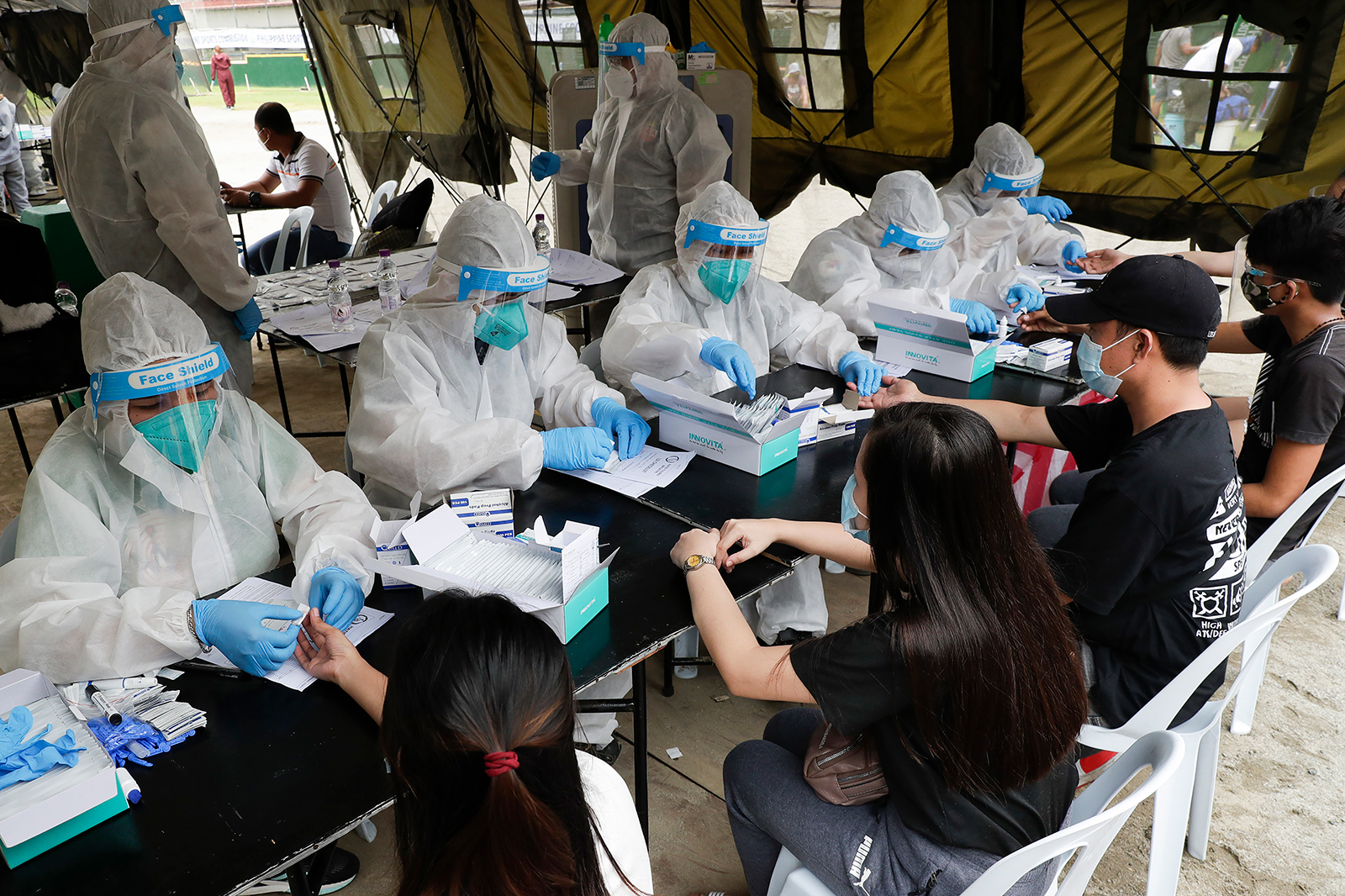 Health workers wearing protective suits perform coronavirus rapid tests on people in Manila, Philippines, on July 28