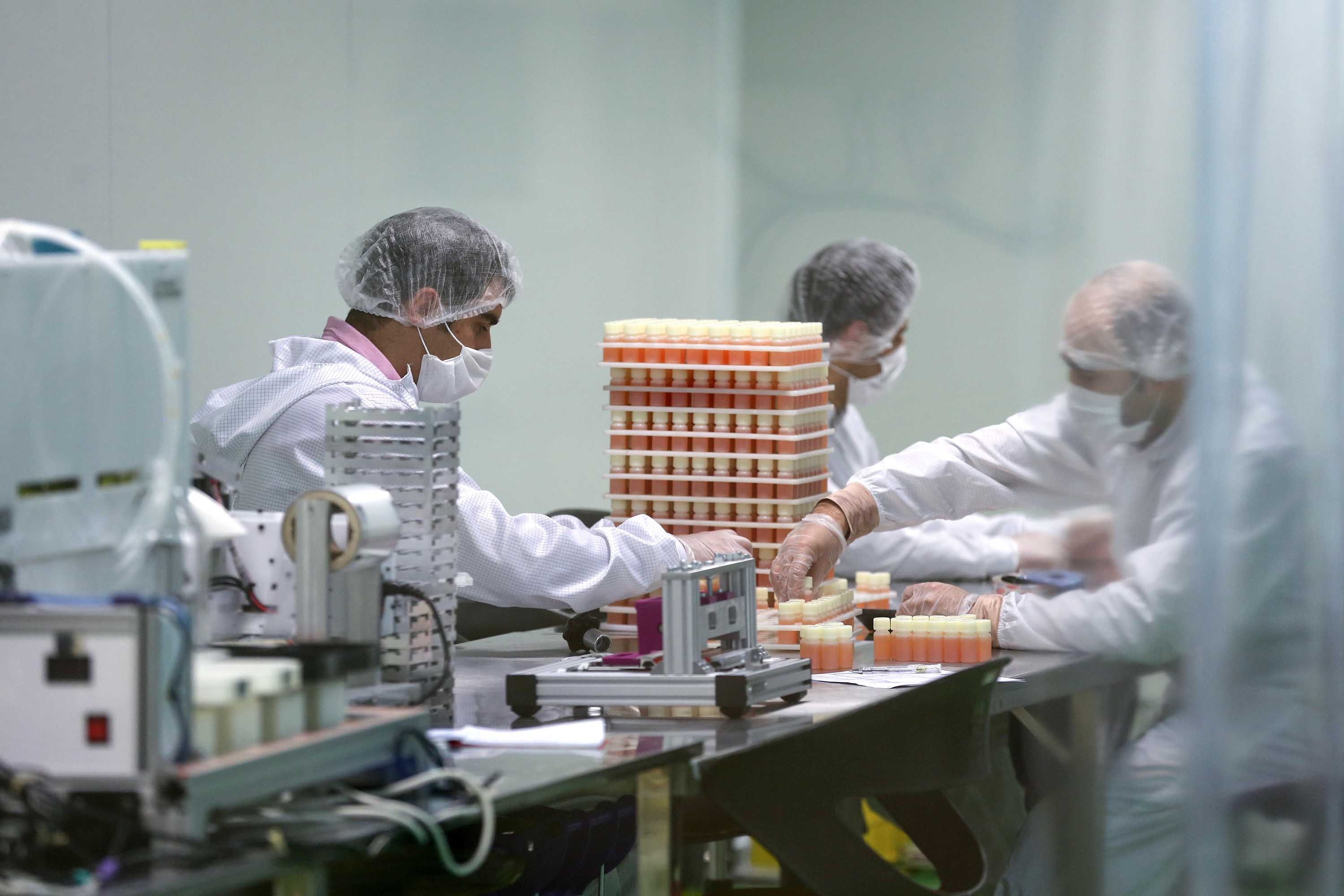 Medical staff work on the production of COVID-19 testing kits in Karaj, Iran, on April 11.