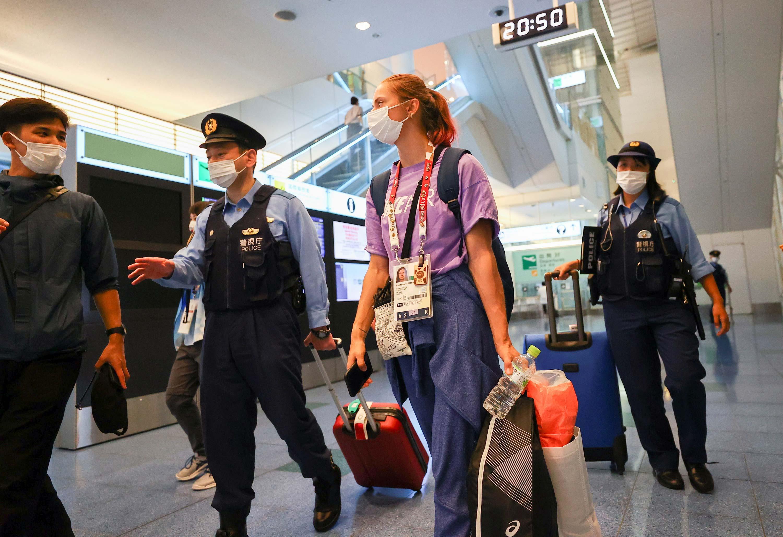 Belarusian athlete Kristina Timanovskaya is escorted by police officers at Haneda International Airport in Tokyo on August 1.