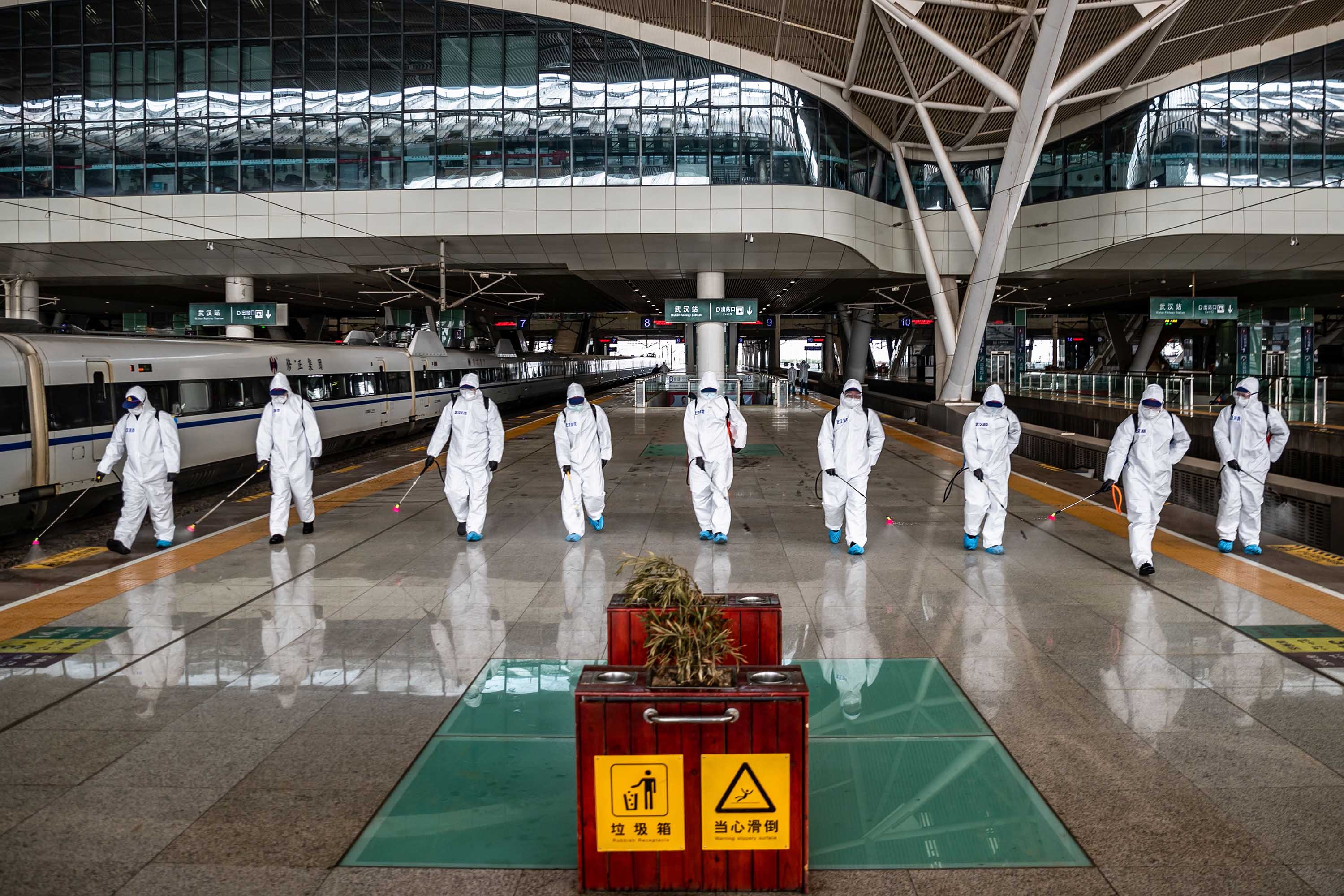 Workers spray disinfectant at Wuhan Railway Station in China's Hubei province on March 24. China has announced that lockdown measures would be lifted for many in the province from Wednesday, and in the provincial capital of Wuhan f April 8.