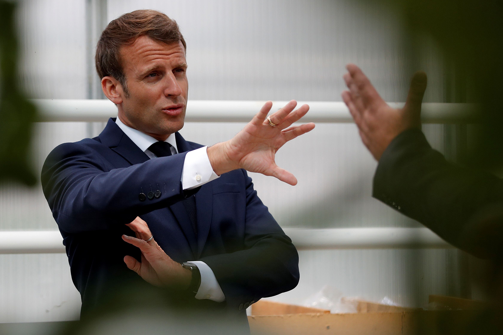 French President Emmanuel Macron talks to farmers and workers during a visit to a greenhouse at the Roue farm in Cleder, western France on April 22.