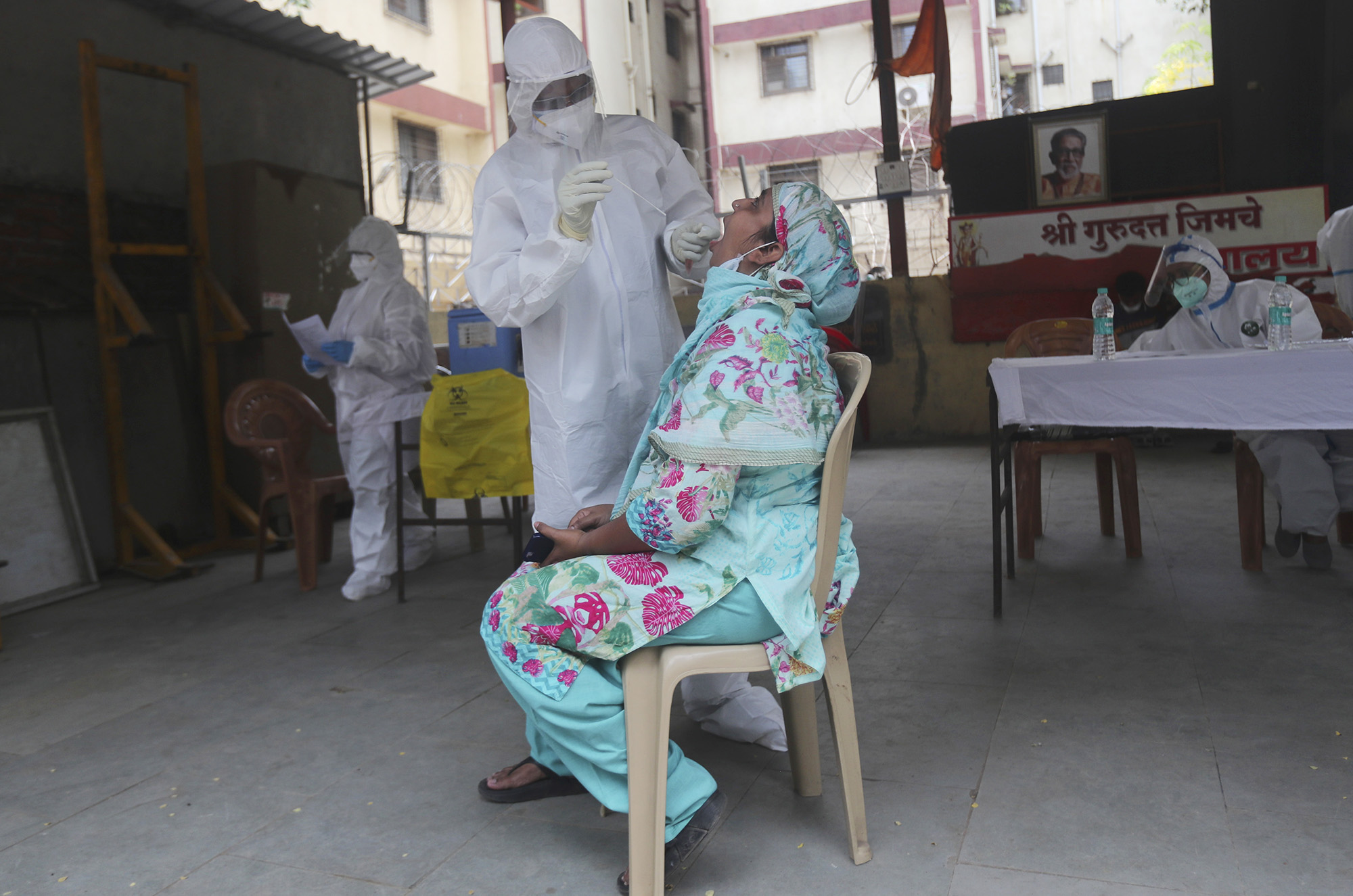 A health worker takes a swab test for the novel coronavirus of a woman during a free medical checkup in Mumbai, India, on Friday, June 26.