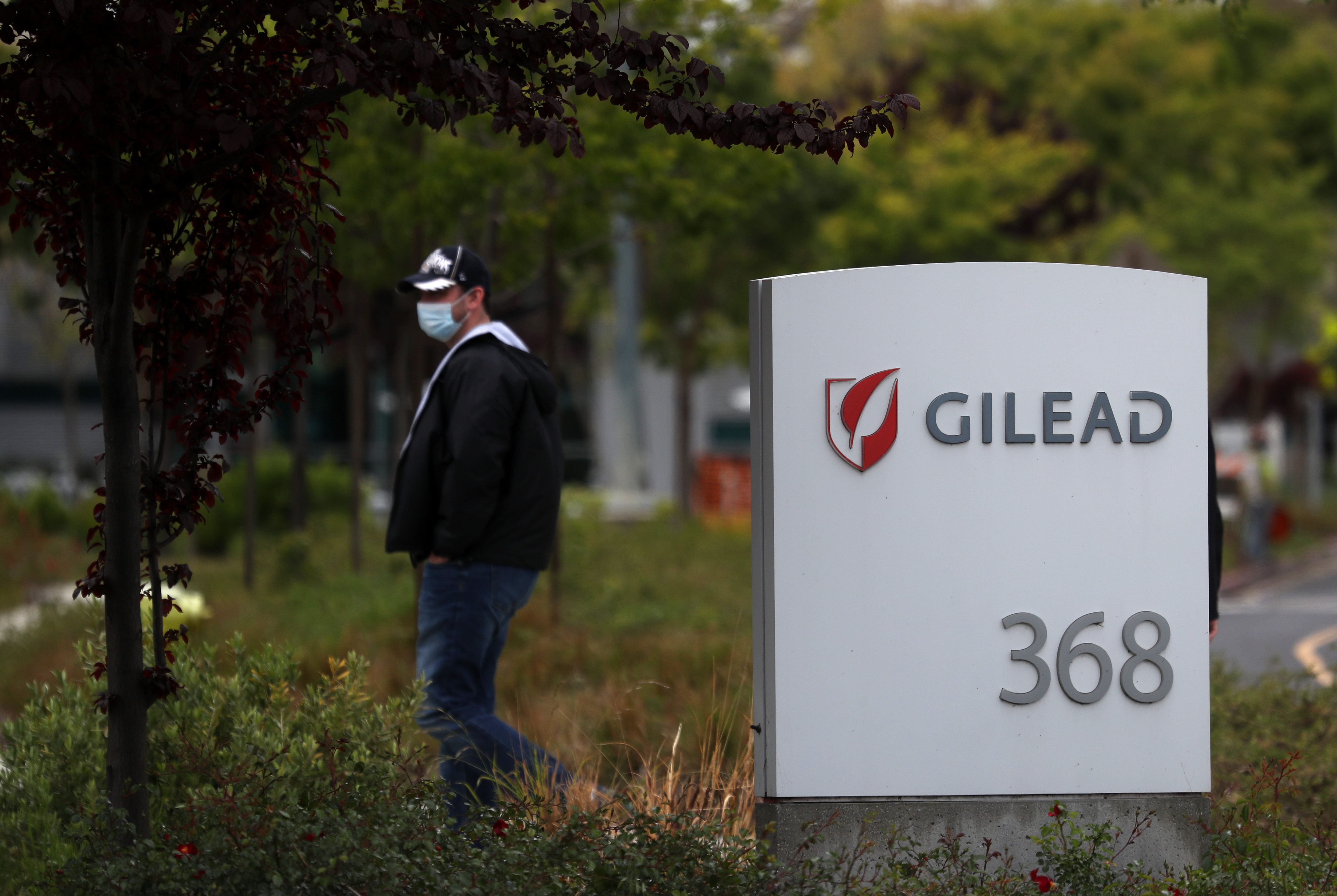 A man walks by the Gilead Sciences headquarters in Foster City, California, on April 29.