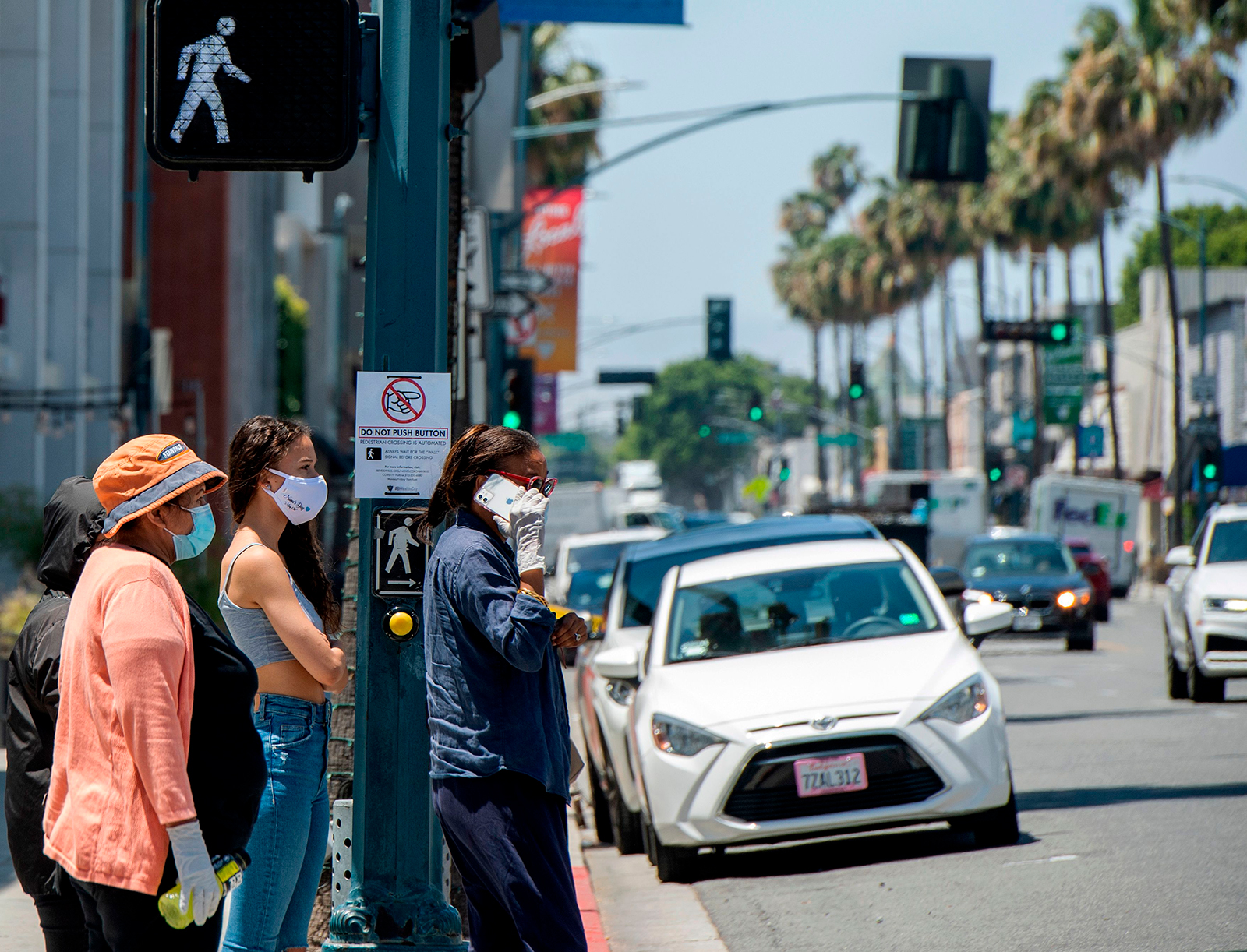 People wait to cross the street on Rodeo Drive where a sign is displayed asking pedestrians not to push the crosswalk button, on May 26, in Beverly Hills, California.