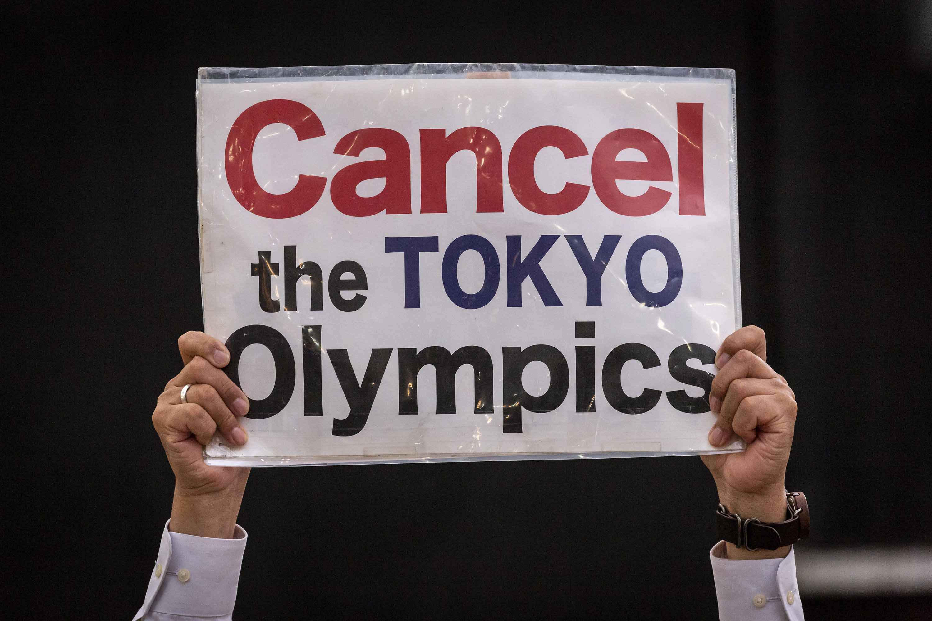 A protester holds a placard during a demonstration against the Tokyo Olympics on Monday, May 17, in Tokyo, Japan.