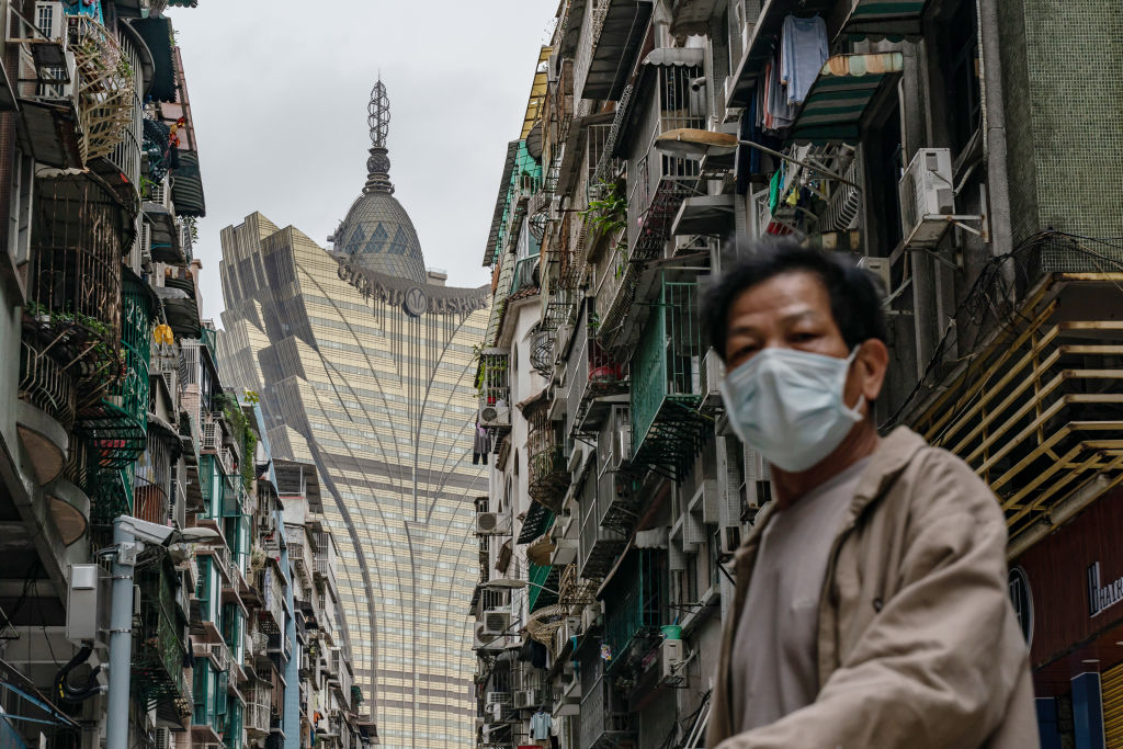 A man wearing a face mask walks across a street in front of the Grand Lisboa Hotel in Macau on February 5, 2020.