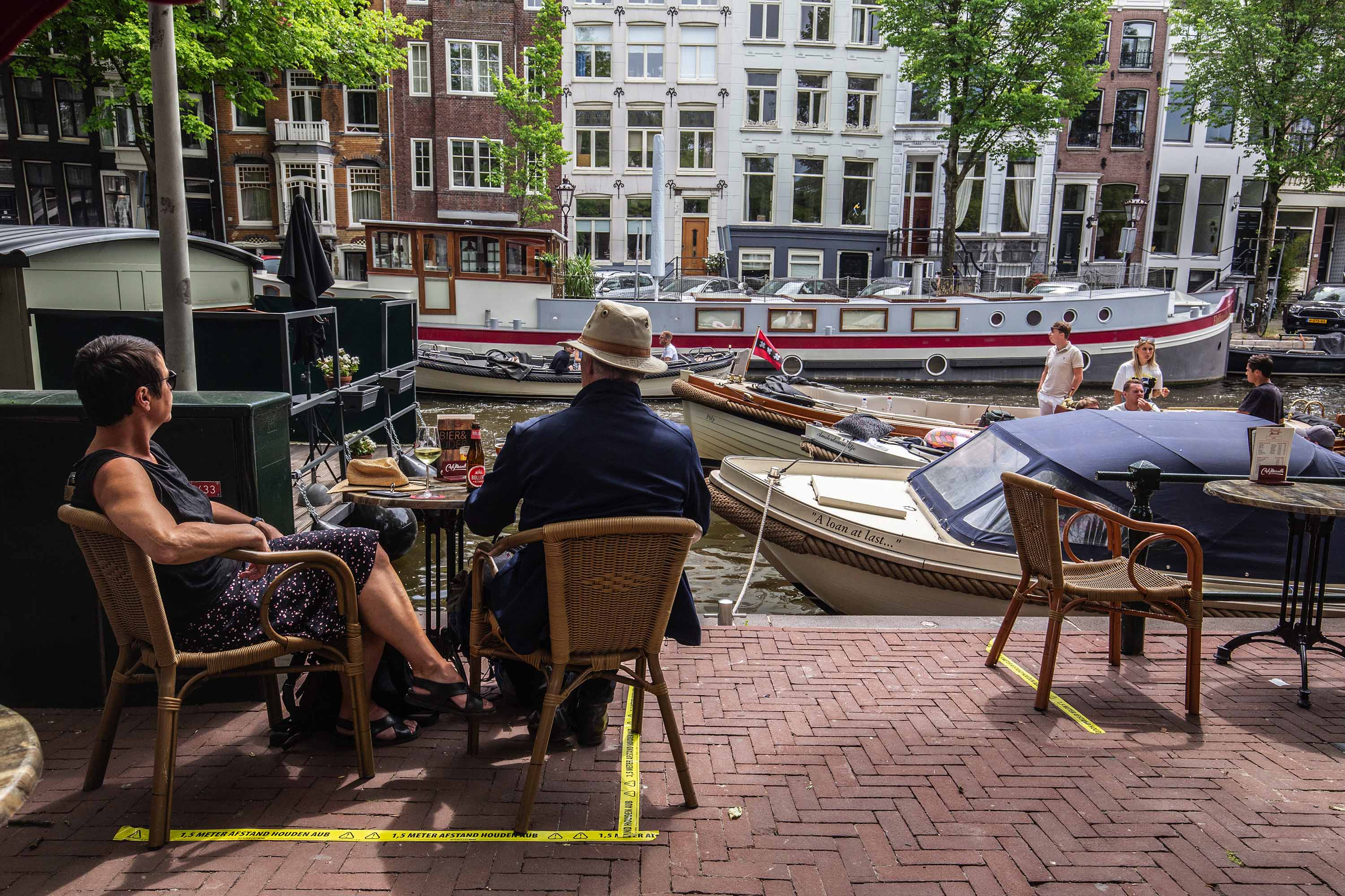 Customers sit at tables with social distancing tape markers at a cafe in Amsterdam, Netherlands, on Monday, June 1.
