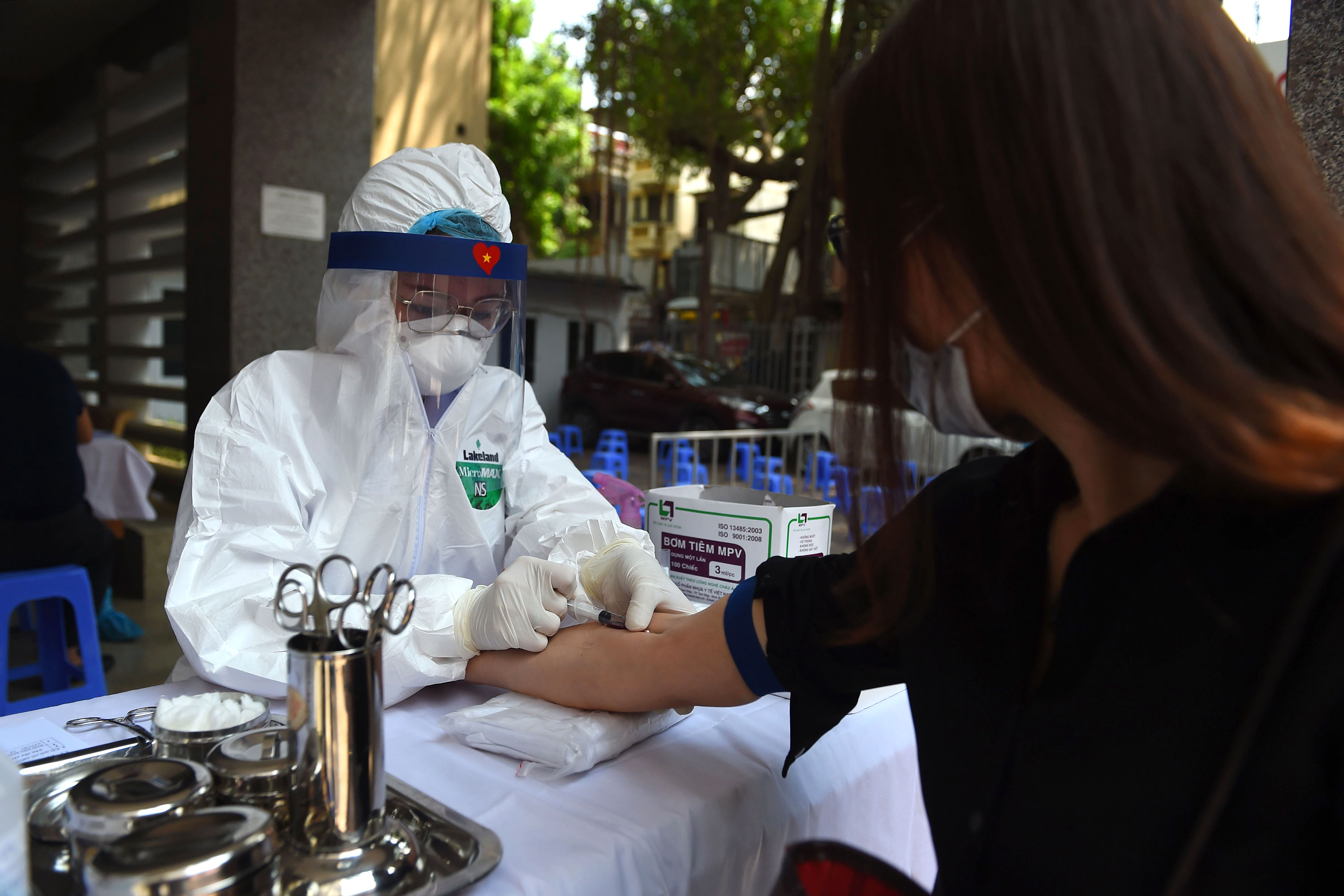 A health worker takes a blood sample from a resident at a coronavirus rapid testing center on July 30 in Hanoi, Vietnam.