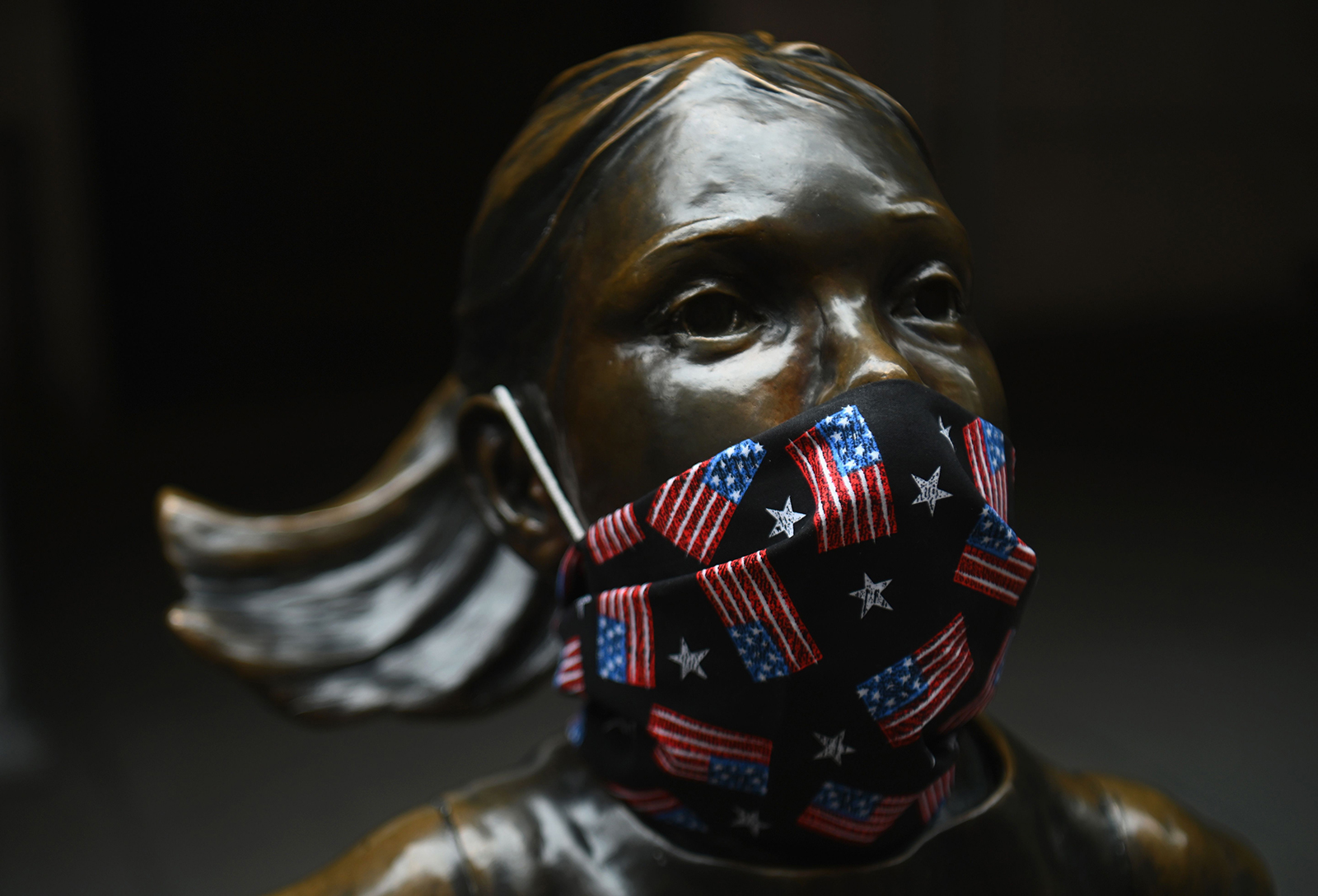 "The ""Fearless Girl"" statue wears a face mask with American Flags outside the New York Stock Exchange at Wall Street on April 23, in New York City."