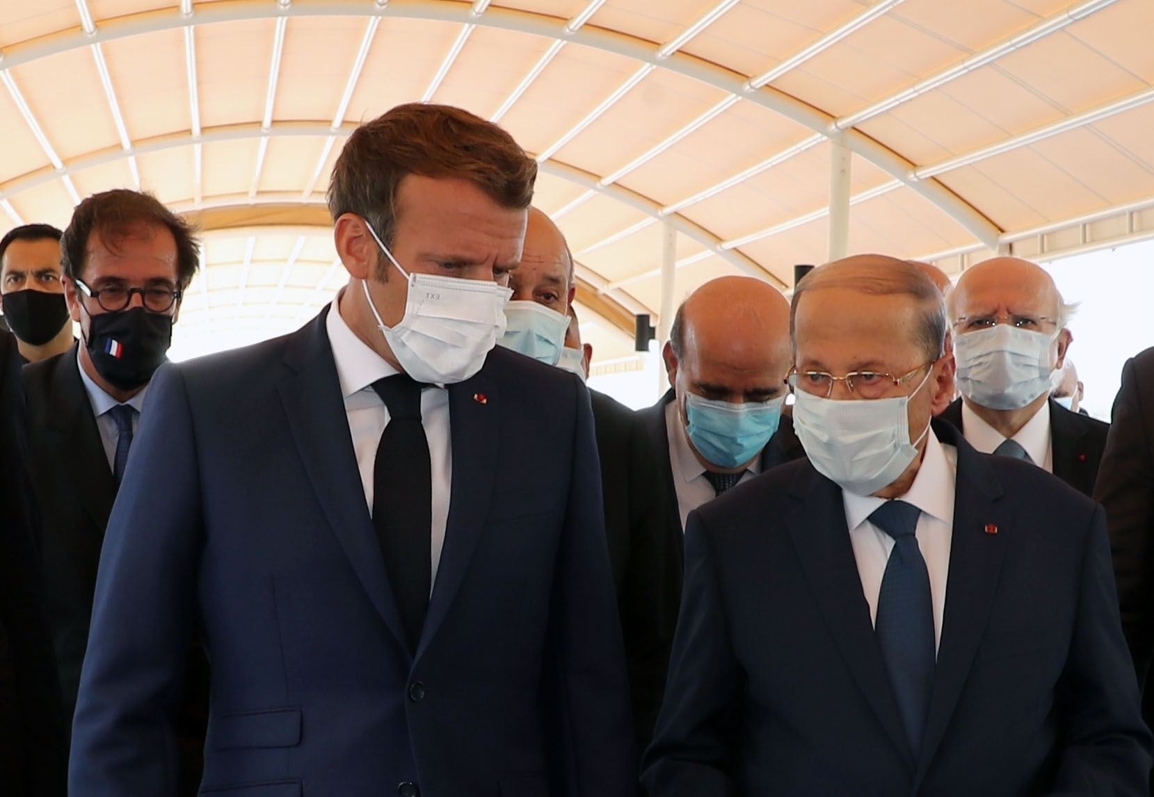 French President Emmanuel Macron, left, walks with Lebanese President Michel Aoun at Rafic Hariri International Airport in Beirut, Lebanon, on August 6.
