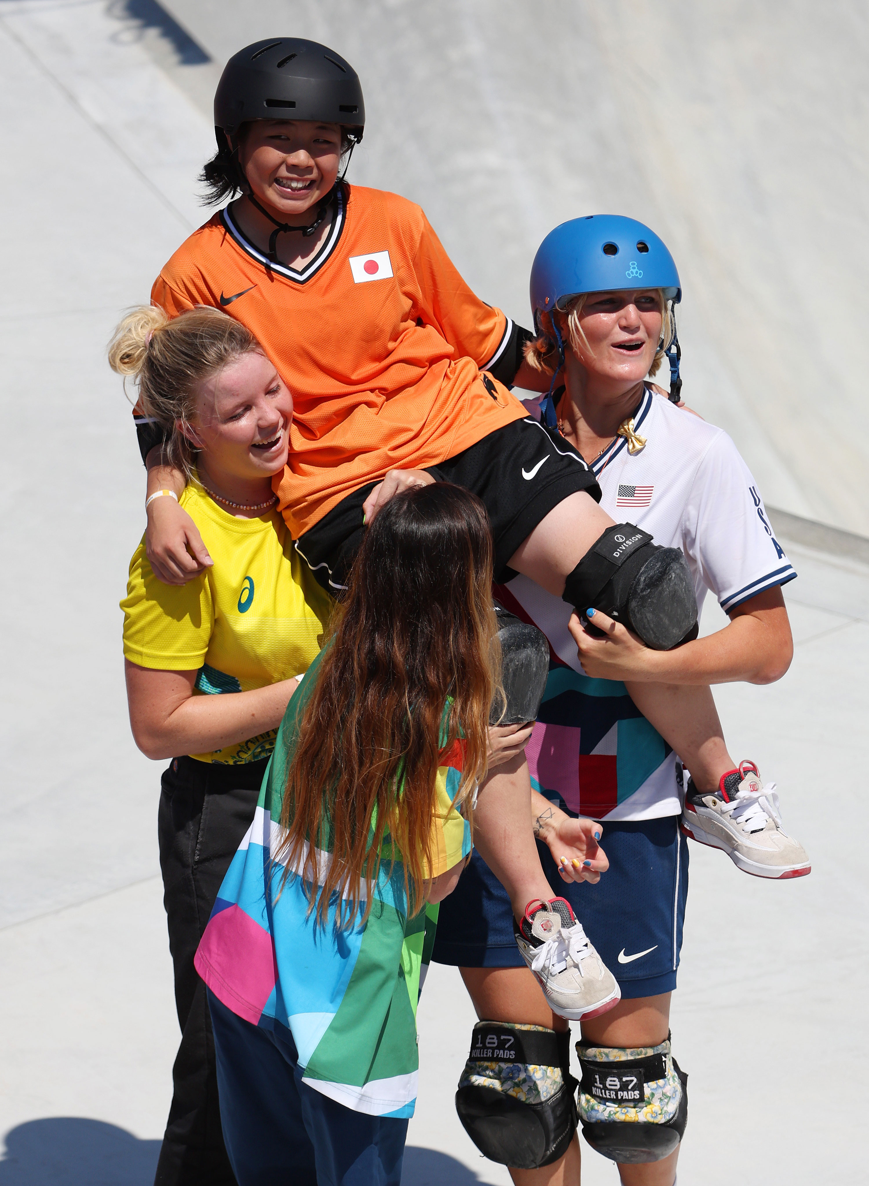 Misugu Okamoto of Japan is carried by Poppy Olsen of Australia, left, and Bryce Wettstein of the United States, right, after Okamoto fell and failed to get a bronze medal in the park skateboarding finals on Wednesday.