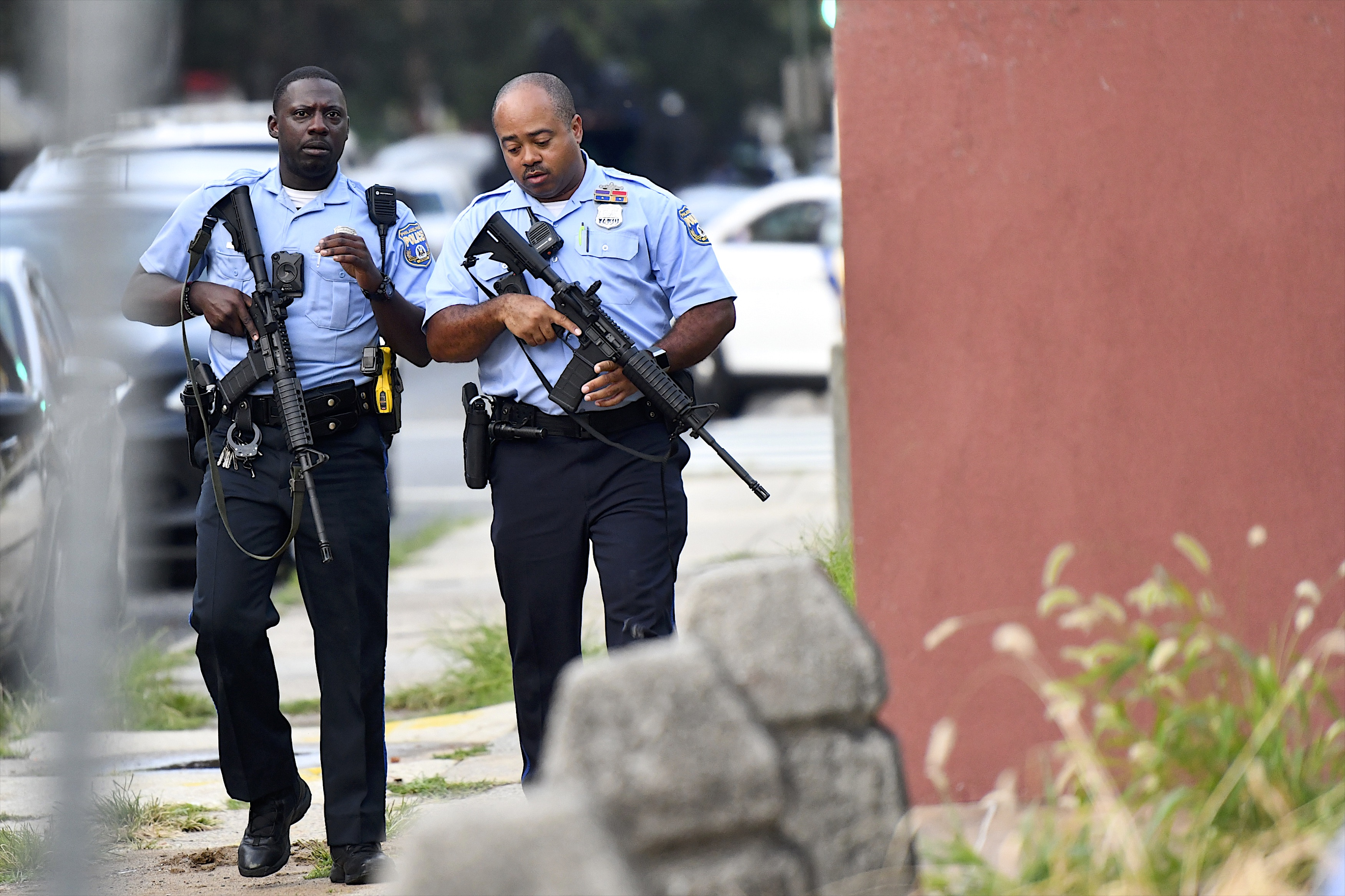 Police officers carrying assault rifles respond to a shooting on August 14, 2019 in Philadelphia.