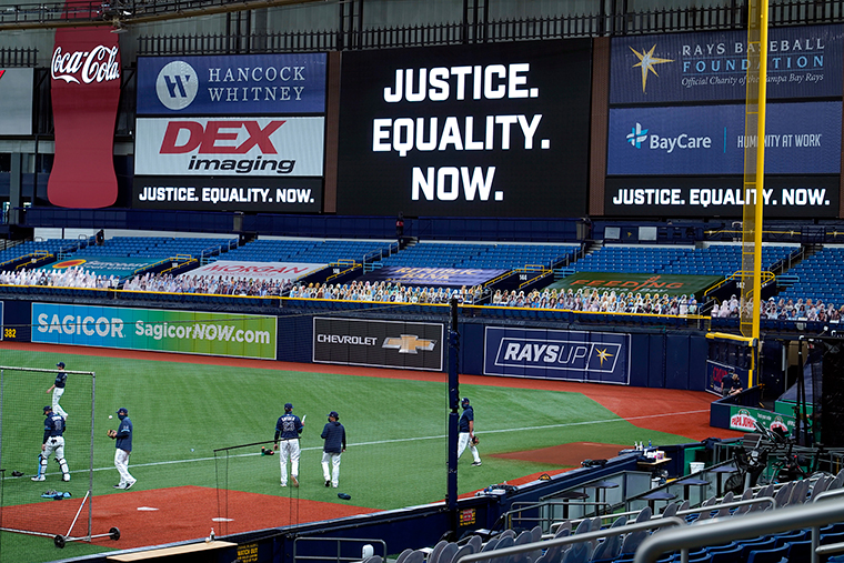 """Tampa Bay Rays players warm up near a """"Justice. Equality. Now."""" sign on the videoboard on Thursday, August 27, in St. Petersburg, Florida."""