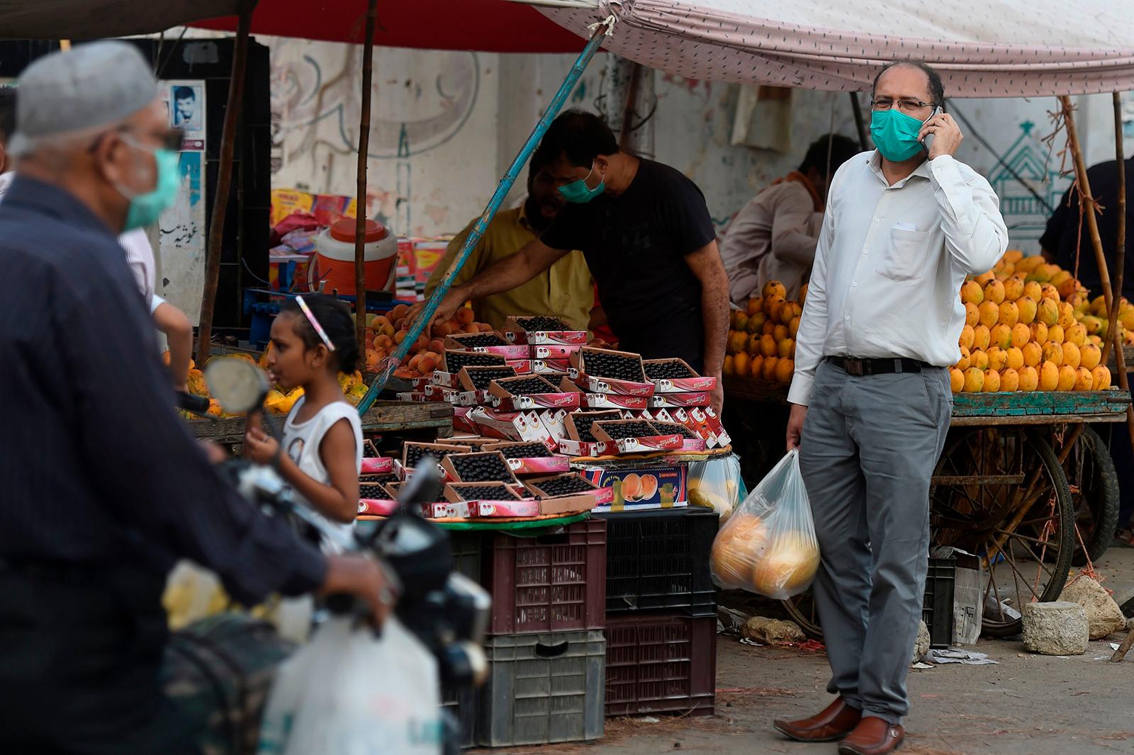 People wearing facemasks buy fruit in Karachi, Pakistan, on June 2.