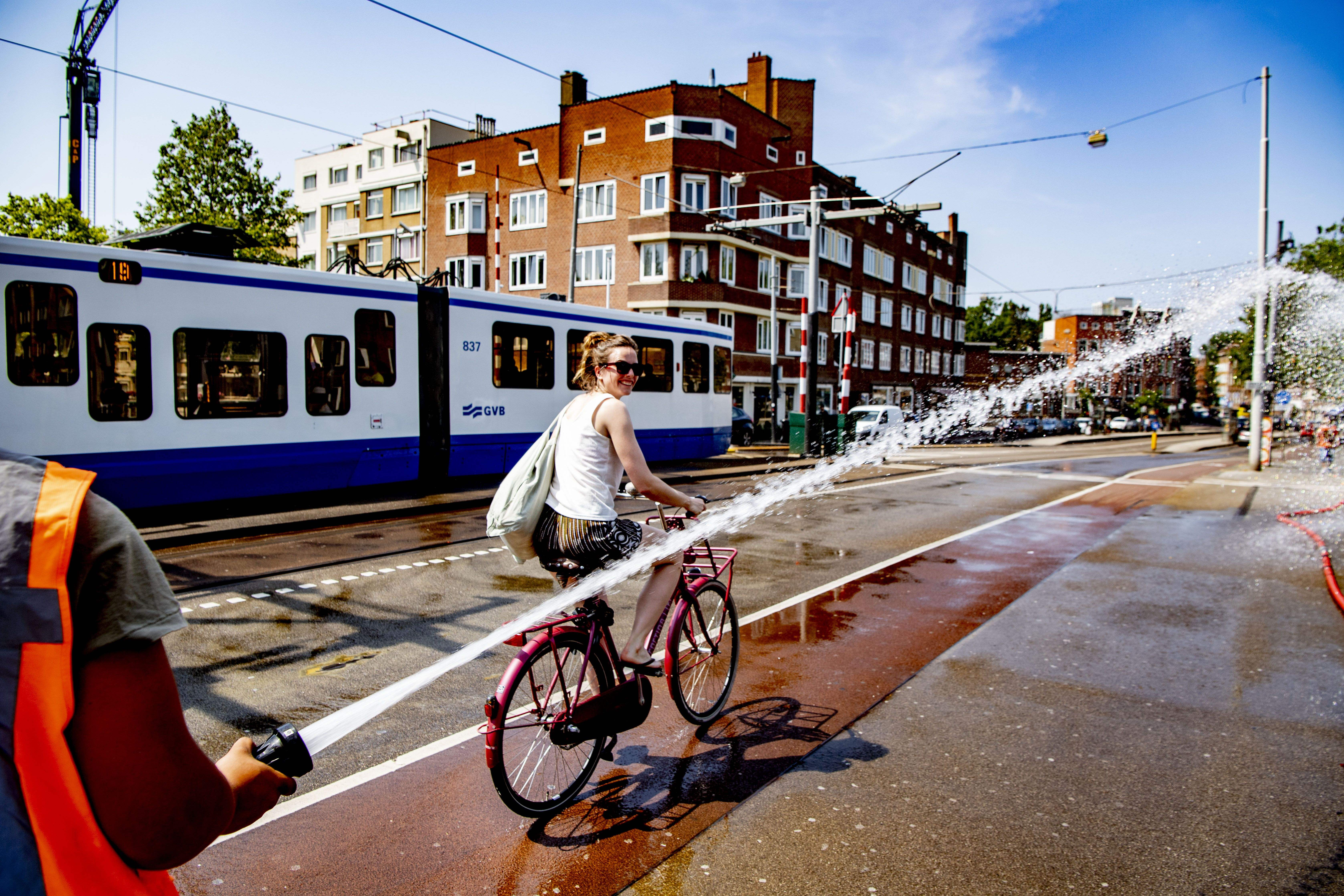A firefighter sprays water as a woman rides her bicycle on the Wiegbrug bridge during a heat wave in Amsterdam on July 25, 2019.