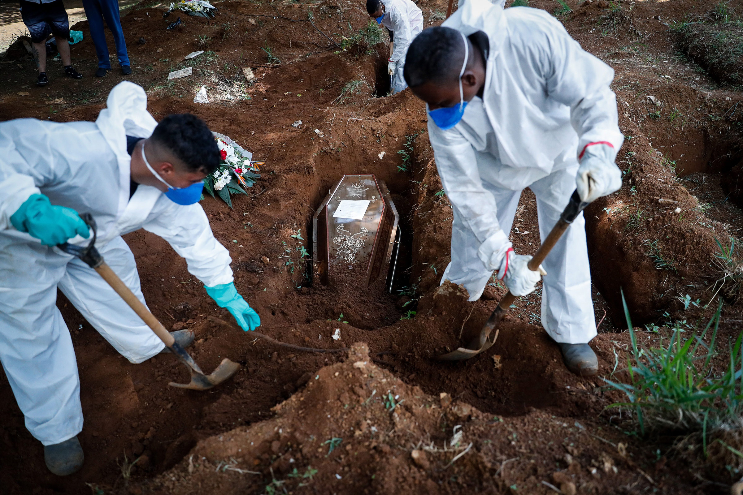 Workers carry out the burial of a Covid-19 victim at the Vila Formosa Cemetery in Sao Paulo, Brazil, on March 11.