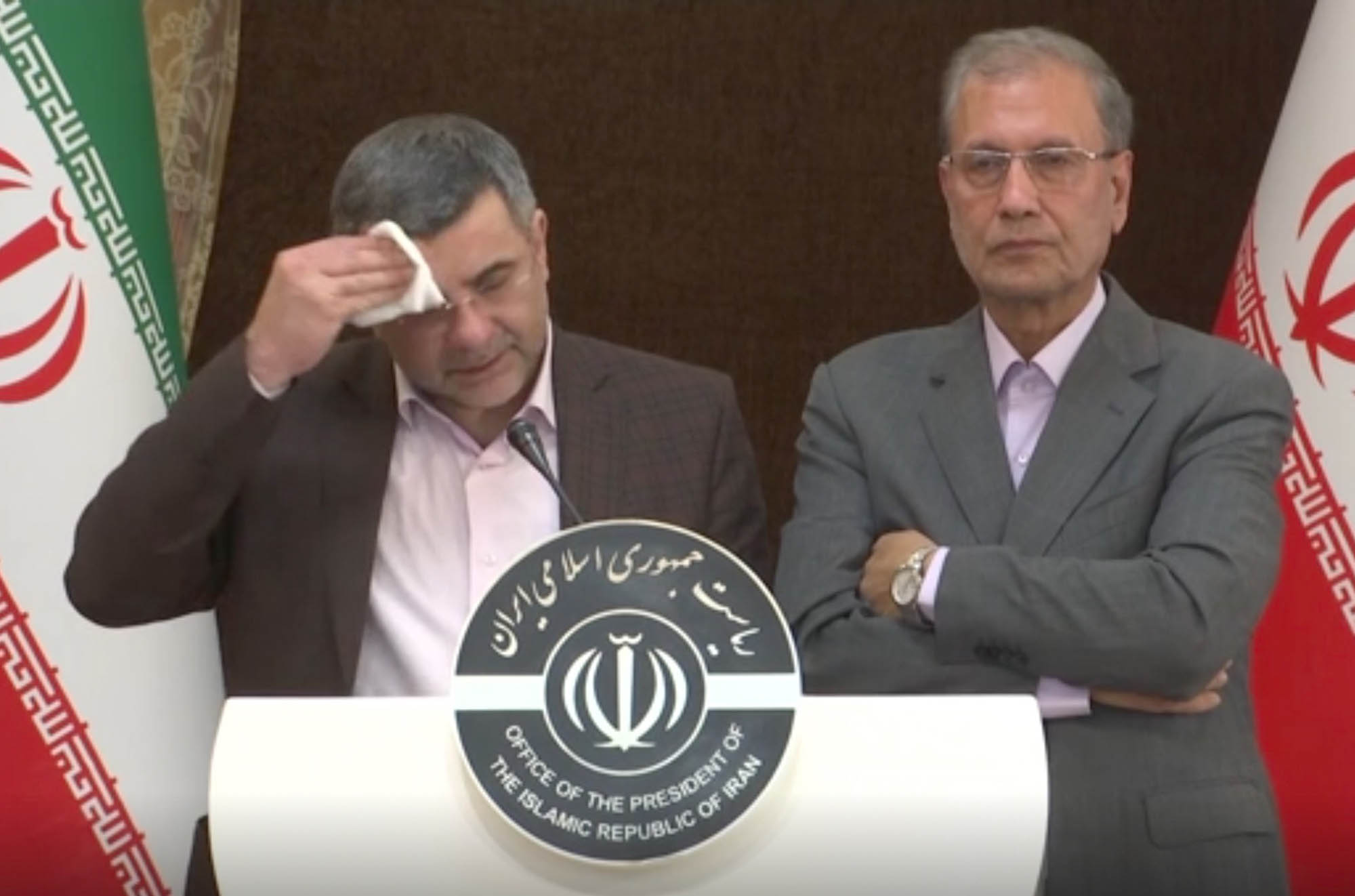 This image made from video shows the head of Iran's counter-coronavirus task force, Iraj Harirchi, left, wiping his face during a press briefing with government spokesman Ali Rabiei, in Tehran, Iran, on Monday. Harirchi, has tested positive for the virus himself, authorities announced on Tuesday, amid concerns the outbreak may be far wider than officially acknowledged.