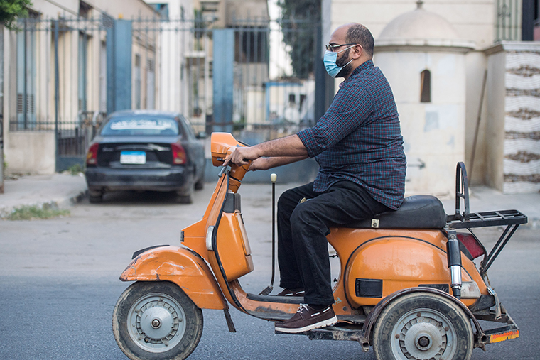 A man wearing a face mask is seen riding a moped along a street in Cairo, Egypt, on Oct. 14, 2020.