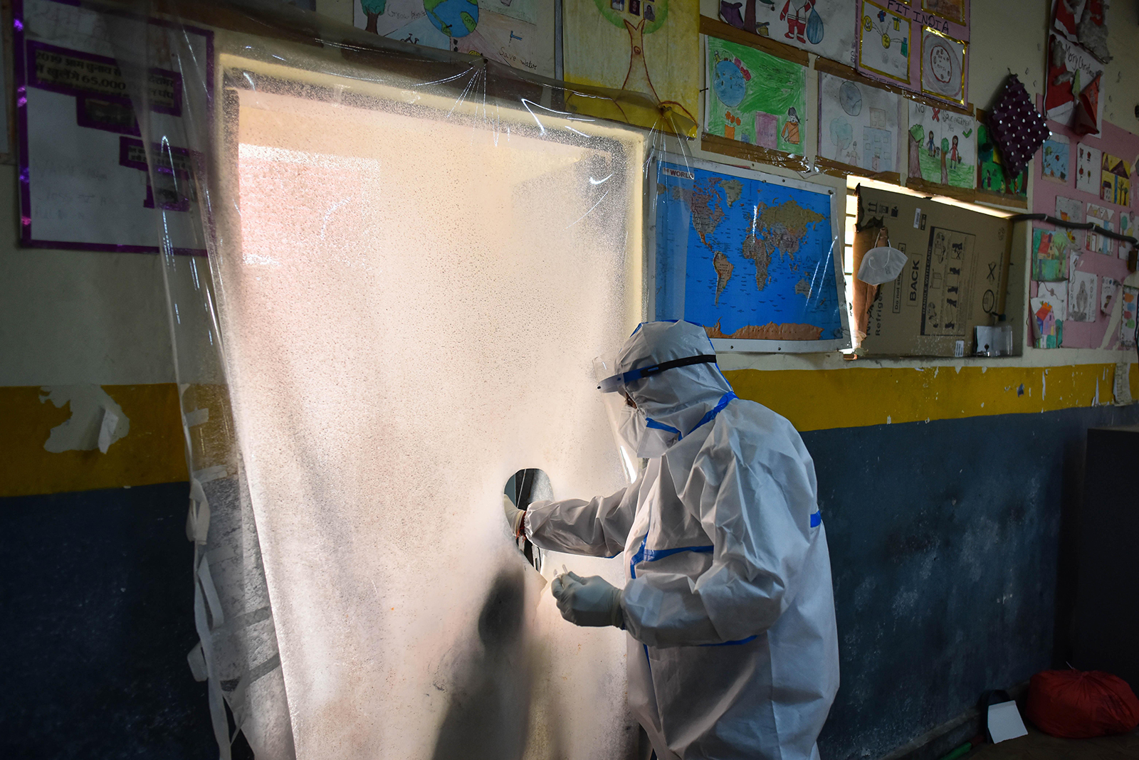 A health worker in PPE coveralls collects a swab sample from behind a protective screen for coronavirus testing, at Khajur Khas in New Delhi, India, on October 28.