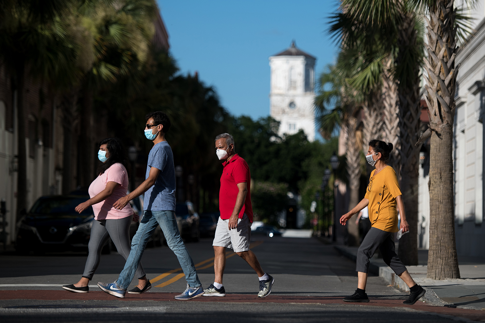 People wearing protective face masks walk along King St. on July 18, in Charleston, South Carolina.