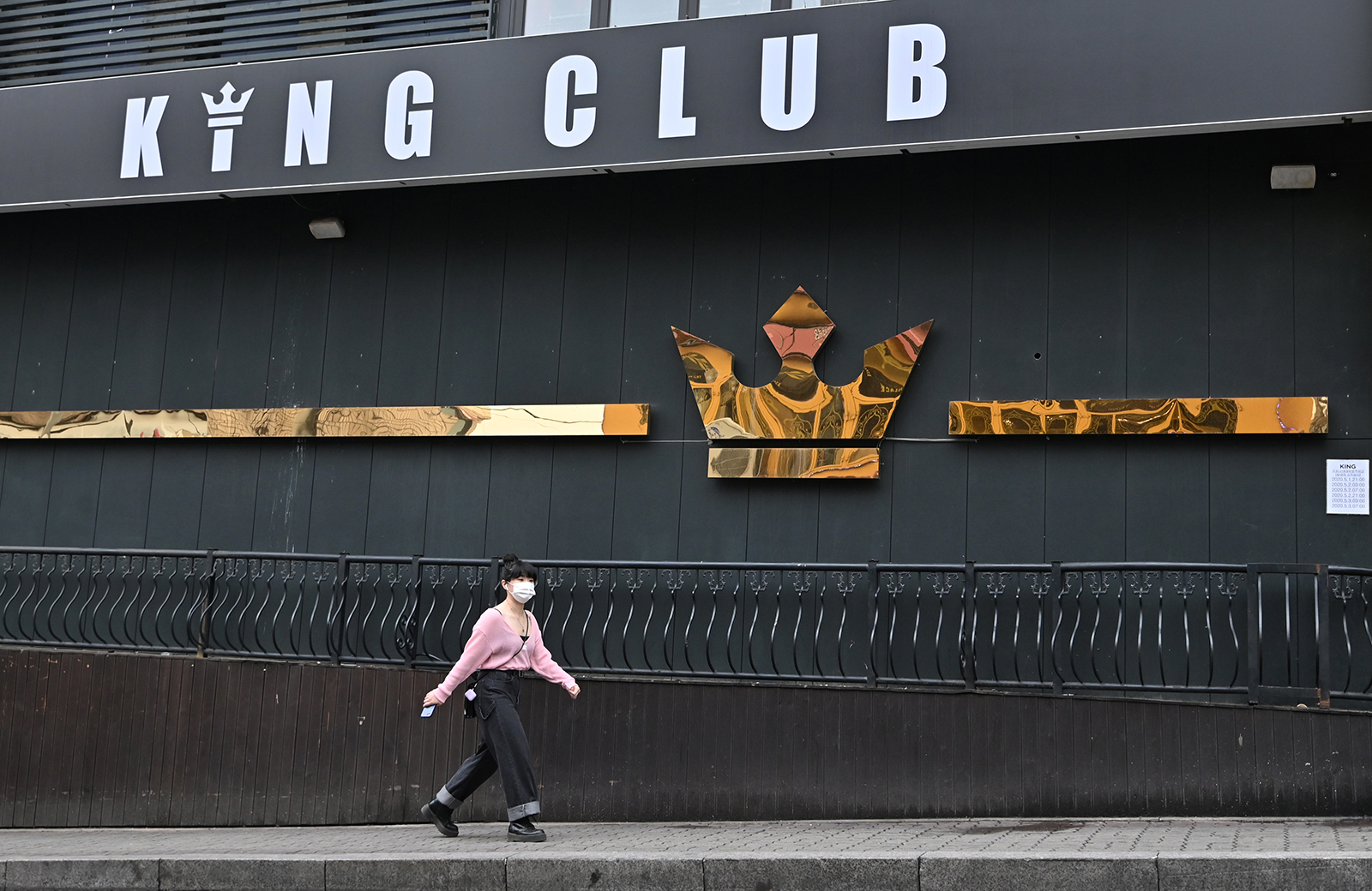 A woman wearing a face mask walks past a night club, now closed following a visit by a confirmed Covid-19 patient, in the popular nightlife district of Itaewon in Seoul on May 10.