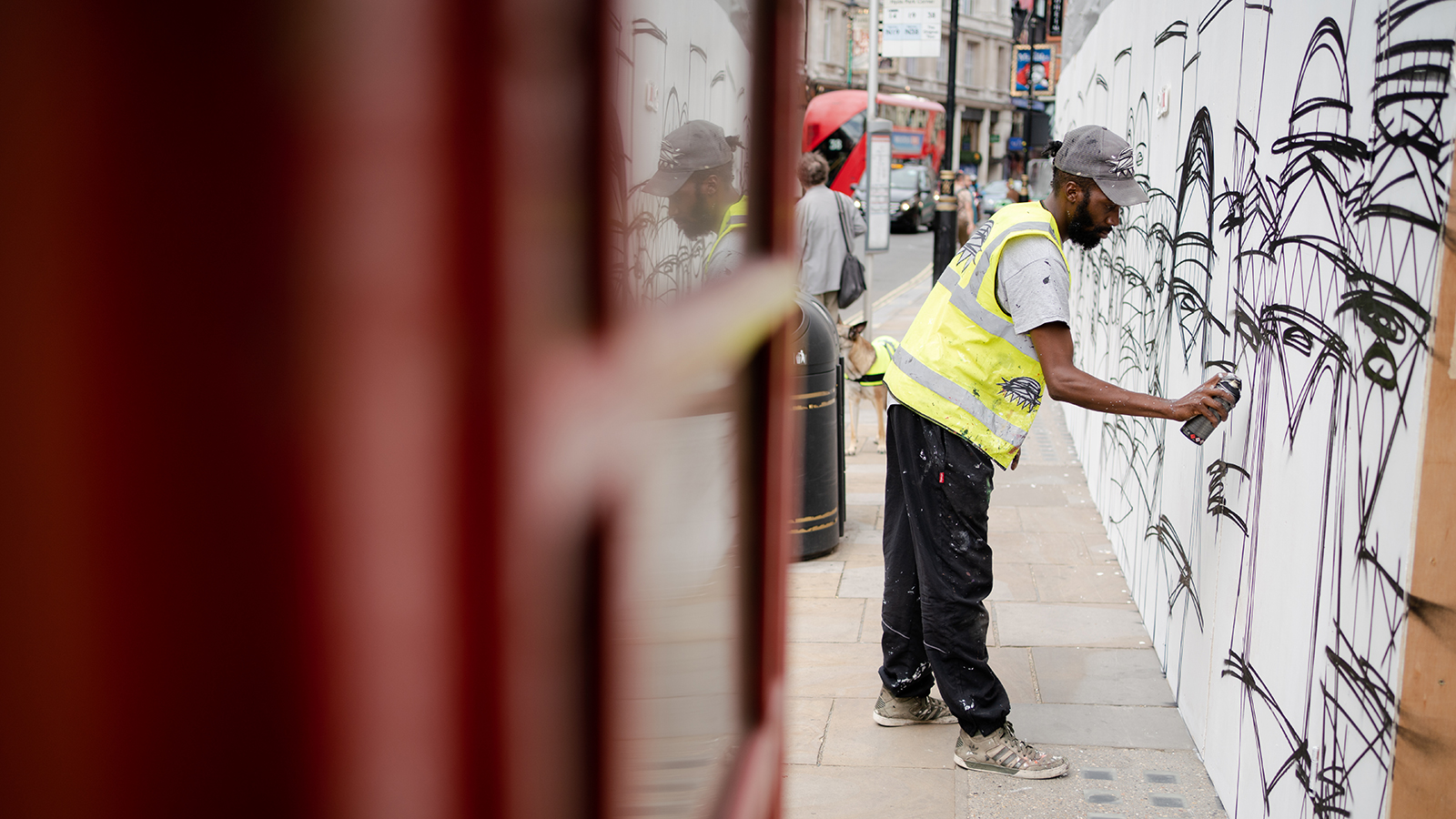 Street artist Nathan Bowen is pictured working on an image in London on Friday.
