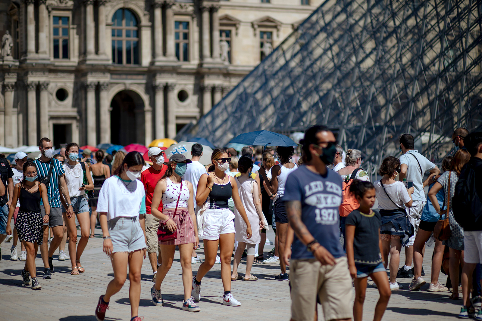People walk past the Louvre Museum in Paris, on August 12.