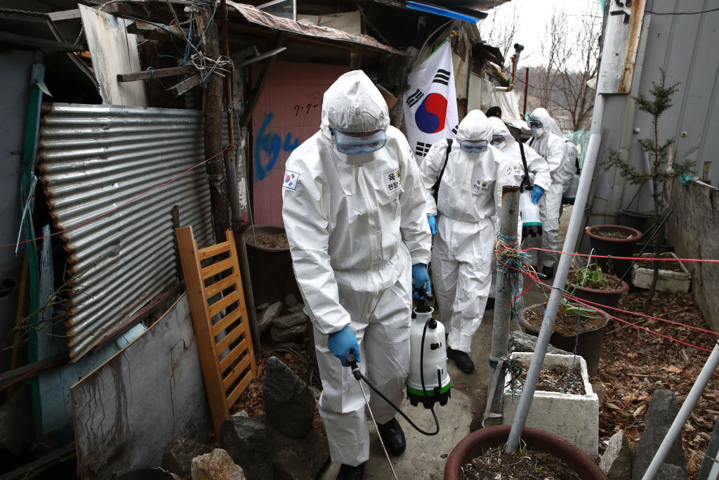 South Korean soldiers wearing protective gear spray antiseptic solution against the coronavirus at the Guryong village encampment in Seoul today.