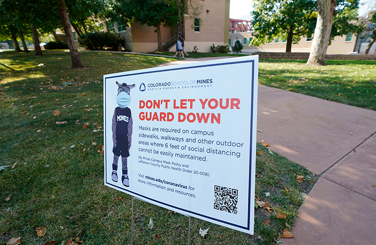 A sign stands along a walkway calling for students and instructors to avoid the new coronavirus at the Colorado School of Mines Wednesday, Sept. 30, 2020, in Golden, Colorado.