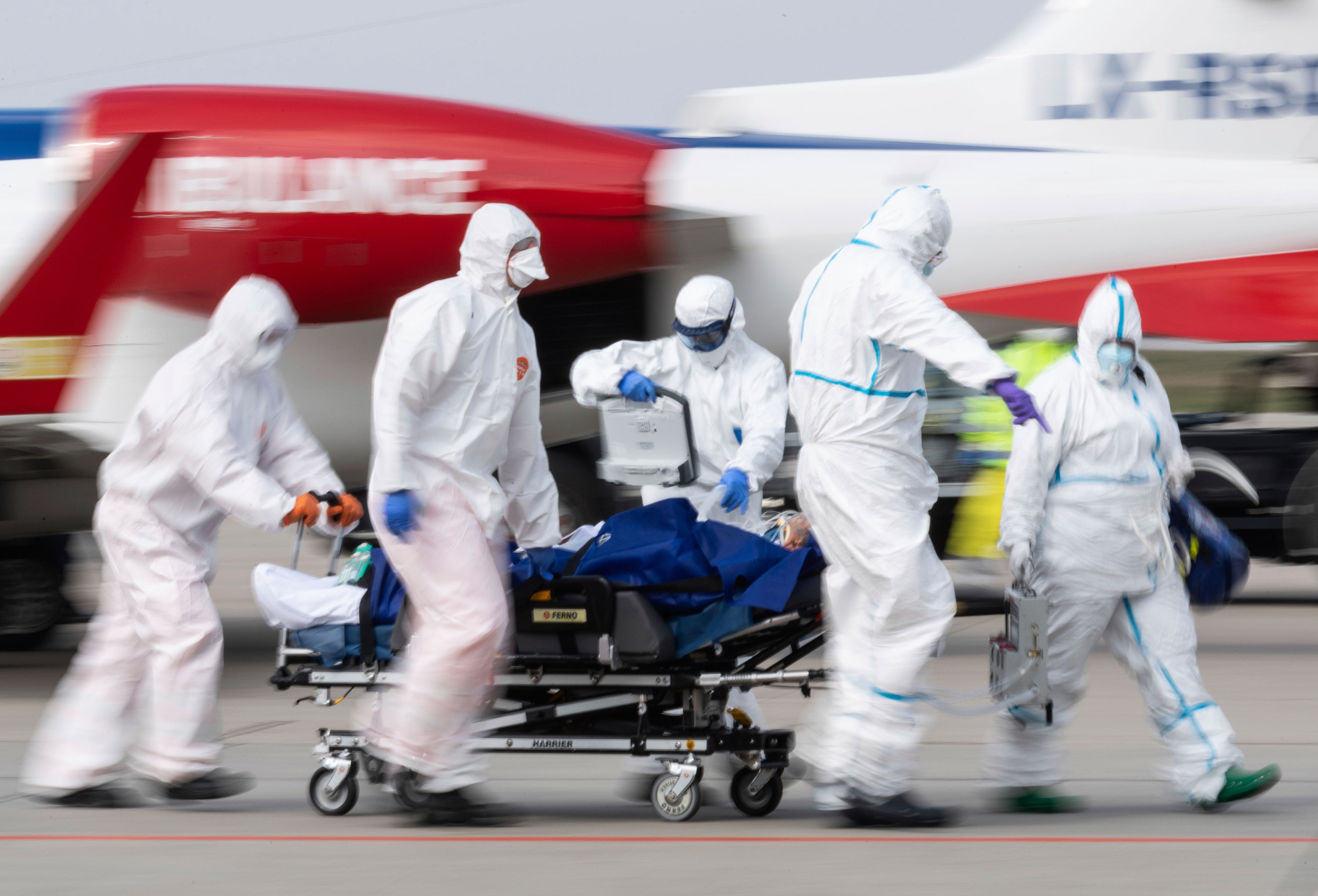 A coronavirus patient is transported from an ambulance plane after landing at Dresden International Airport in Dresden, Germany, on April 4.