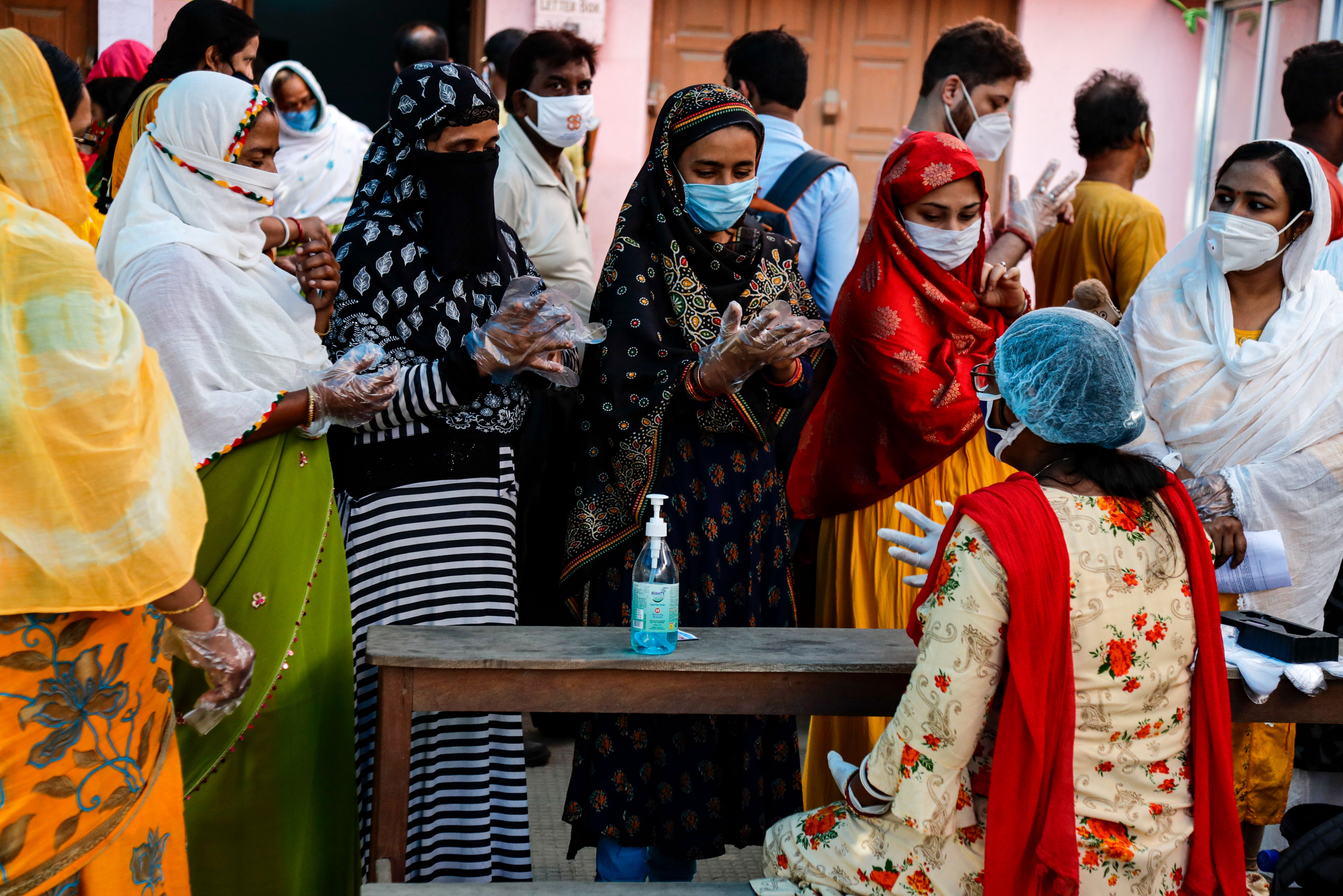 People wear gloves before casting their votes at a polling station during West Bengal state elections in New Town, North 24 Parganas district, India, on April 17.