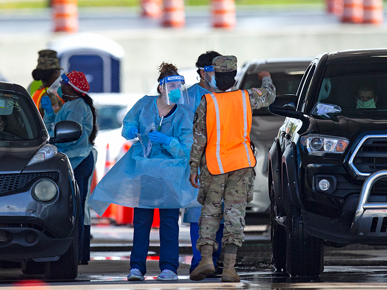 A National Guard troop directs cars as people are tested by healthcare workers at the COVID-19 drive-thru testing center at Hard Rock Stadium in Miami Gardens on Sunday, July 19.