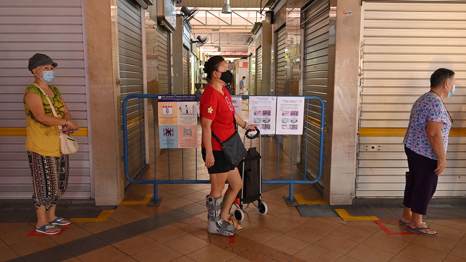 People wearing face masks keep their distance in a queue to enter a wet market in Singapore on April 22.