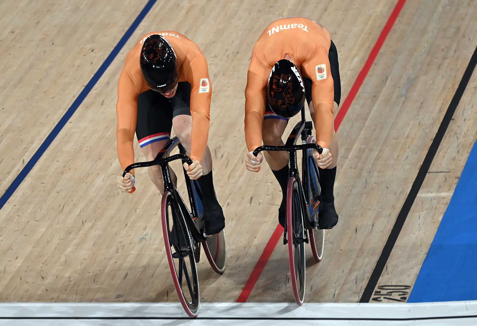 Harrie Lavreysen of the Netherlands, left, crosses the finish line ahead of teammate Jeffrey Hoogland during the men's sprint event on August 6.
