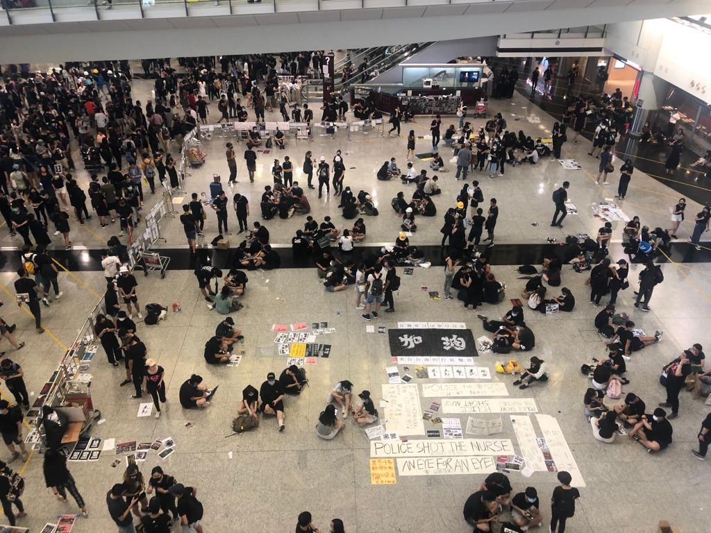 Protesters mill around in the airport, where they have conducted a sit-in for hours.